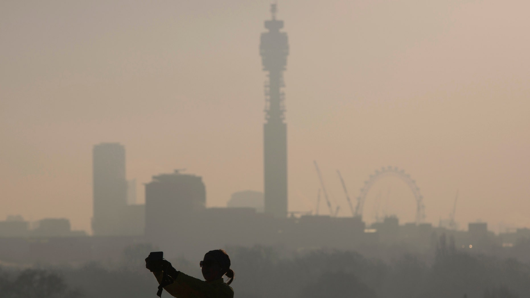 """File photo. A woman takes a """"selfie"""" photograph on a frosty morning in Primrose Hill north in London December 30, 2014."""
