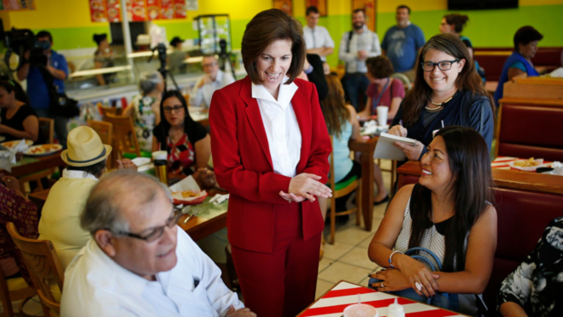 In this May 31, 2016, photo, U.S. Senate candidate Catherine Cortez Masto, center, laughs while speaking with people at a campaign event at a restaurant in Las Vegas. A battle royal is shaping up in Nevada over the open Senate seat created by the retirement of Minority Leader Harry Reid of Nevada. A former state attorney general, Masto, would be the first Latina ever to serve in the U.S. Senate. (AP Photo/John Locher)