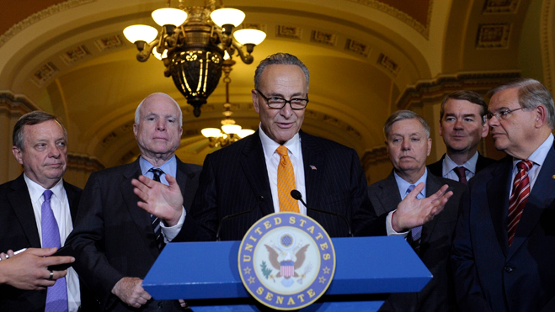Sen. Charles Schumer, D-N.Y., center, speaks following a vote in the Senate on immigration reform on Capitol Hill in Washington, Thursday, June 27, 2013.  (AP Photo/Susan Walsh)