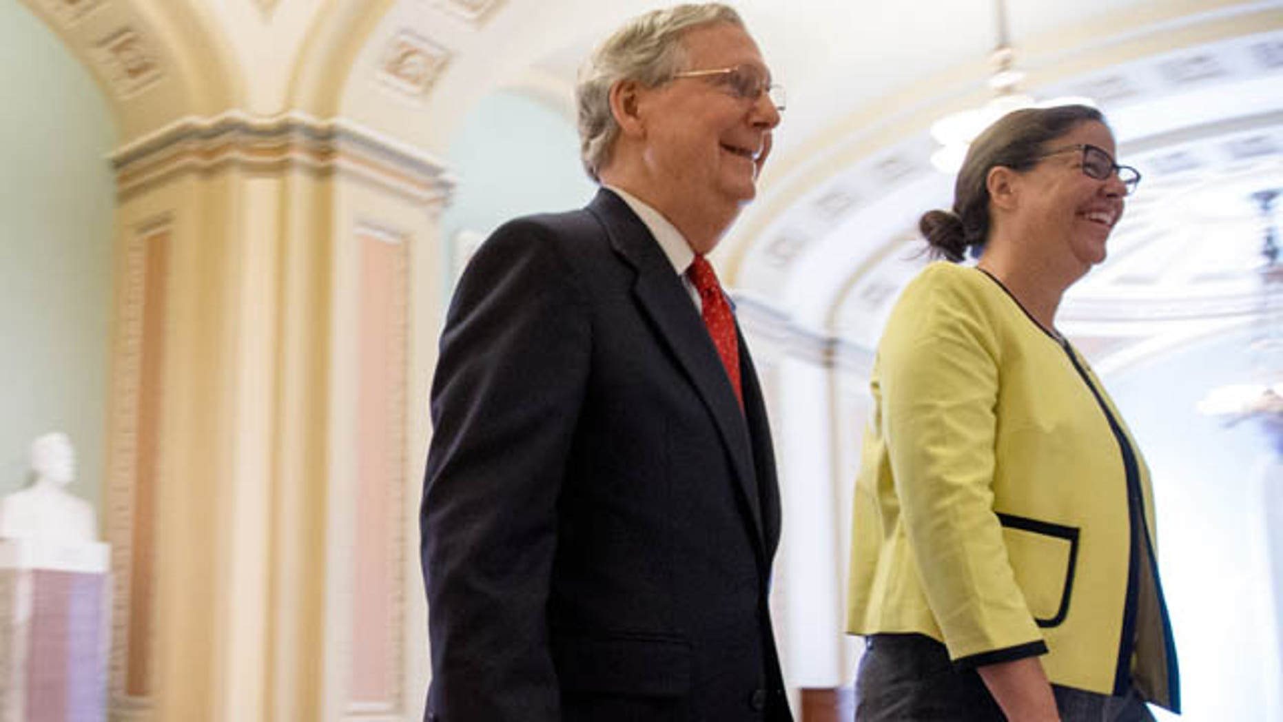 July 26, 2015: Senate Majority Leader Mitch McConnell, R-Ky., left, accompanied by Secretary for the Majority of the Senate Laura Dove, heads into the Senate chamber as the Senate convenes for a Sunday session on Capitol Hill in Washington. (AP Photo/Andrew Harnik)
