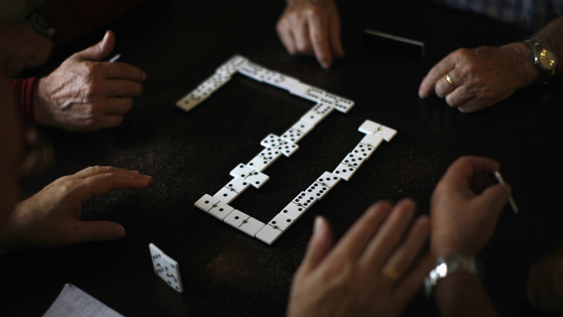 Pensioners play dominoes at a seniors centre during the International Day of Older Persons.