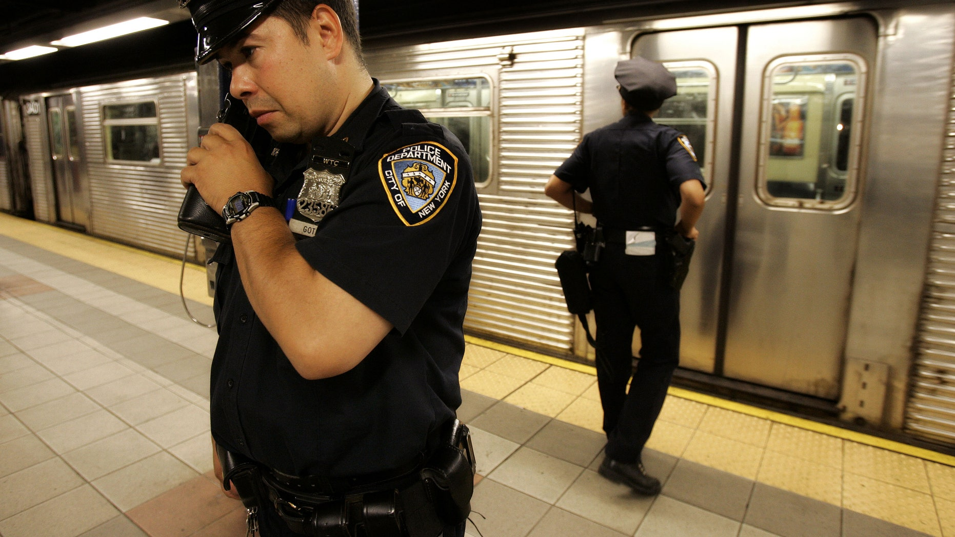 July 8, 2005: New York police officer Frank Gotay listens to a message on his radio as his partner, Yolanda Cortes, waits for a subway car's doors to open while performing random checks along the platform at the 42nd Street station in New York. A decade after the Sept. 11 terror attacks, New York City emergency agencies are better trained and better equipped to communicate in a disaster, but first responders in cities around the country say the progress is not good enough.