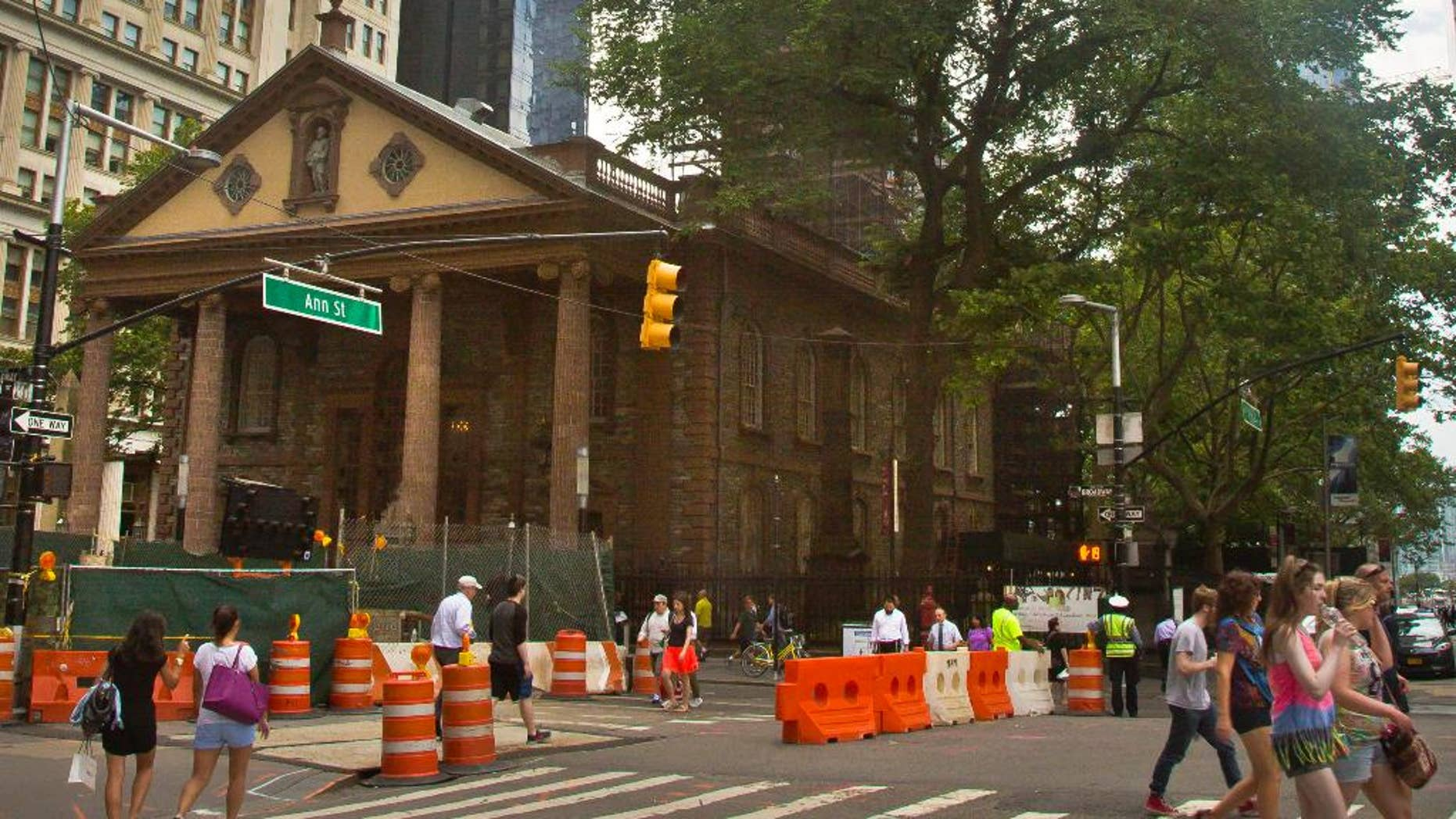"""FILE - In this June 25, 2015, file photo, the World Trade Center, right, looms behind St. Paul's Chapel with its steeple wrapped in scaffolding for repairs, in New York. The winner of a new competition open to people of all faiths called """"The Reconciliation Preaching Prize,"""" has been won by an Army chaplain from Austin, Texas. The Rev. David Peters will have the privilege of delivering an original sermon on Sept. 11, at the chapel near ground zero that was turned into a makeshift memorial shrine and became a place of rest and renewal for volunteers and responders, following the terrorist attacks that brought down the twin towers. (AP Photo/Bebeto Matthews, File)"""