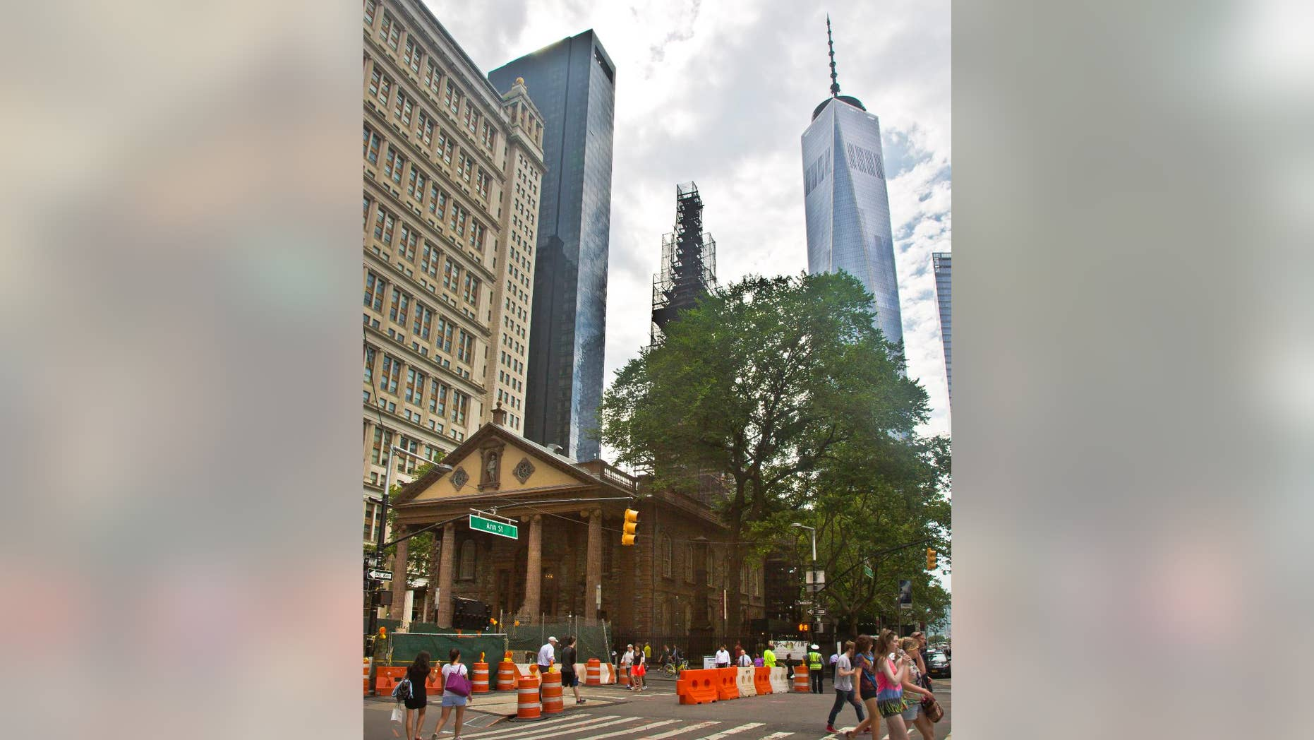 "FILE - In this June 25, 2015, file photo, the World Trade Center, right, looms behind St. Paul's Chapel with its steeple wrapped in scaffolding for repairs, in New York. The winner of a new competition open to people of all faiths called ""The Reconciliation Preaching Prize,"" has been won by an Army chaplain from Austin, Texas. The Rev. David Peters will have the privilege of delivering an original sermon on Sept. 11, at the chapel near ground zero that was turned into a makeshift memorial shrine and became a place of rest and renewal for volunteers and responders, following the terrorist attacks that brought down the twin towers. (AP Photo/Bebeto Matthews, File)"