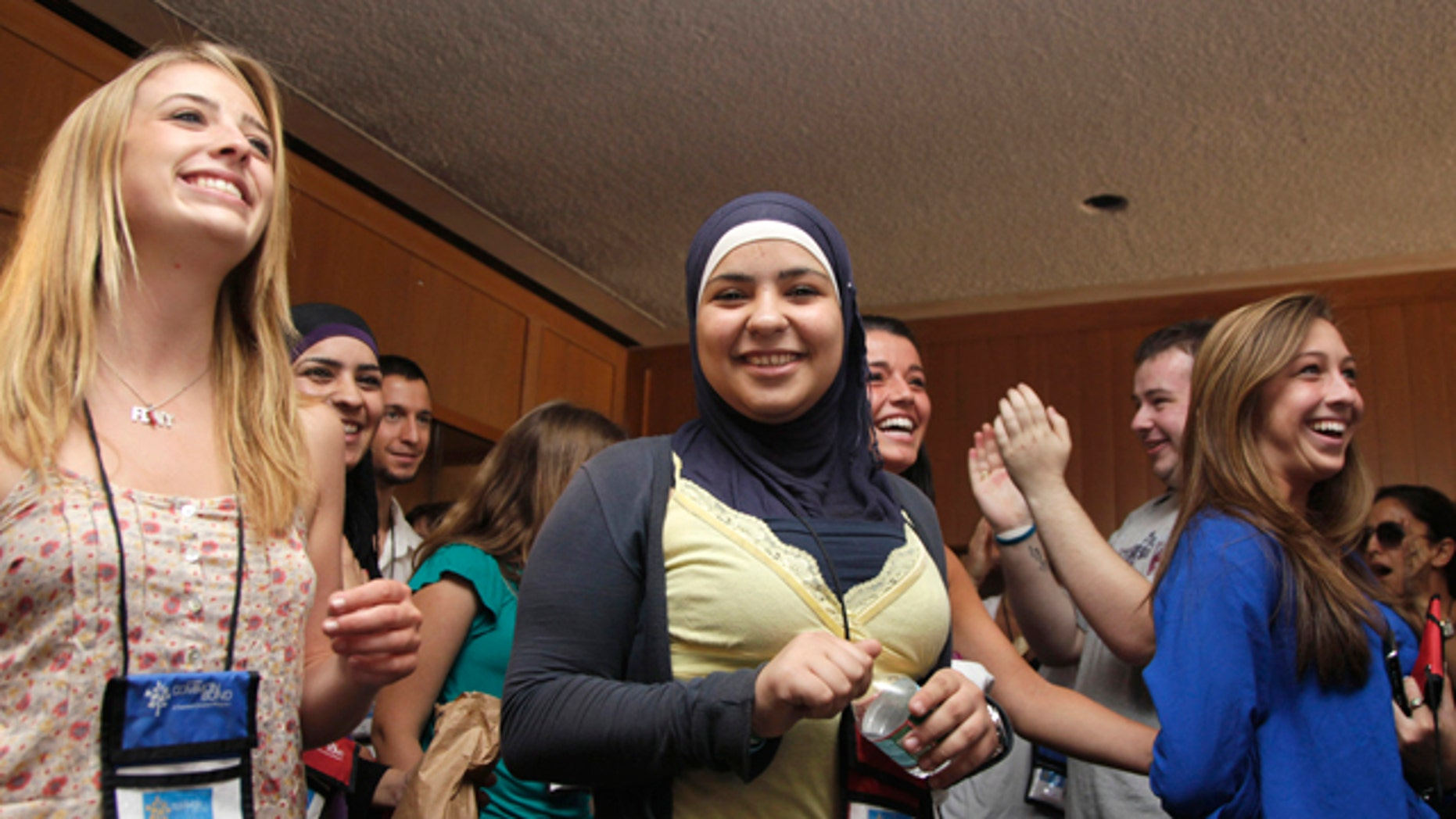 July 27: From left, Caitlin Leavey, of New York, Farrah Sarrawi of Palestine, Francesca Picerno of the US, and Allison Stahlman, are applauded during Project Common Bond on the Foxcroft School campus in Middleburg, Va. Project Common Bond brings together offspring of 9/11 victims with other teens who have lost family members to acts of terror around the world.