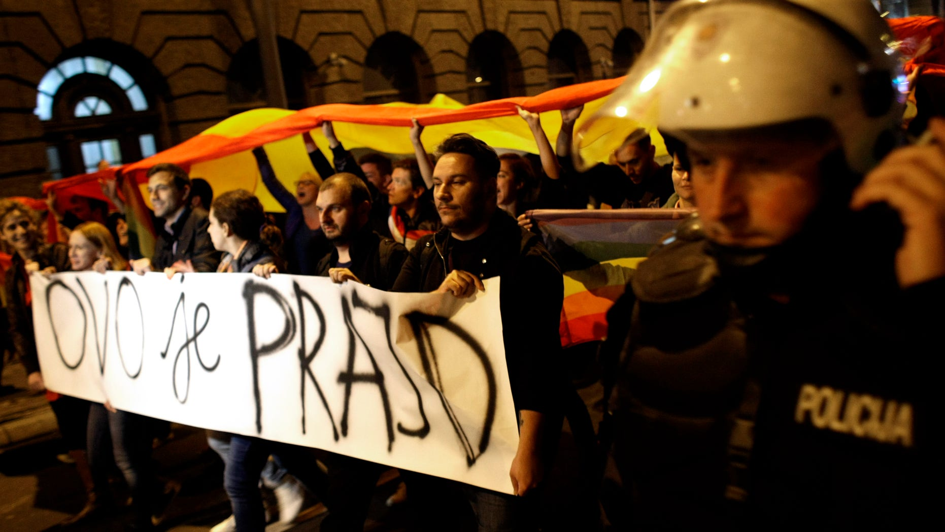 """Sept. 27, 2013: Gay rights activists hold up a large rainbow flag and a banner reading """"This is the Pride"""";  during a protest in Belgrade, Serbia."""