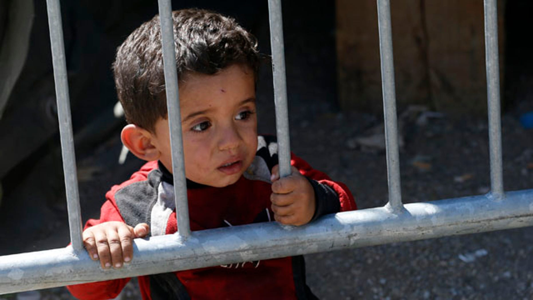 Aug. 24, 2015: A migrant boy looks through fence in a migrant processing center in the southern Serbian town of Presevo. (AP Photo/Darko Vojinovic)