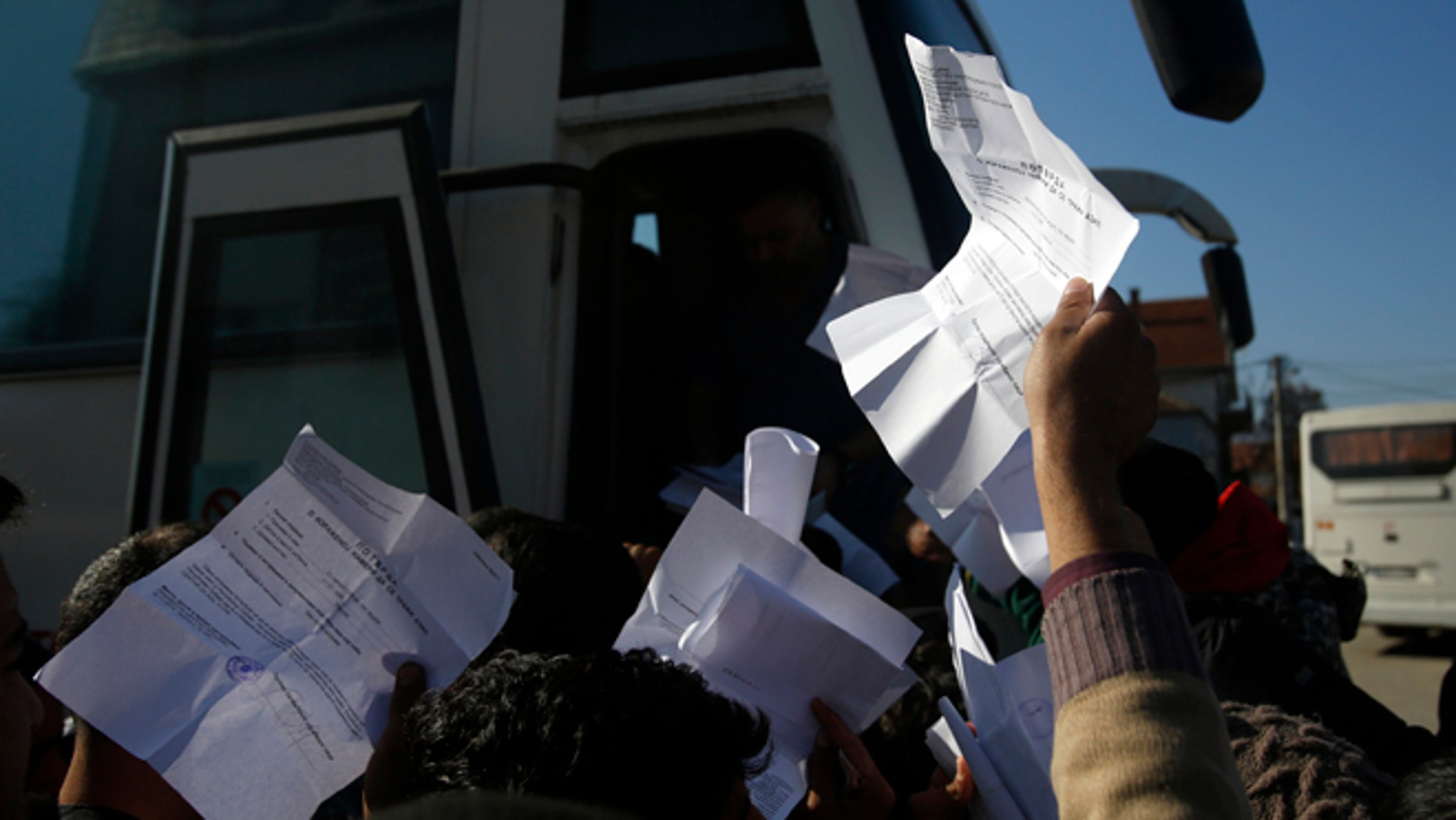 Migrants showing registration papers issued by Serbian authorities, try to get a seat on a bus in the southern Serbian town of Presevo.