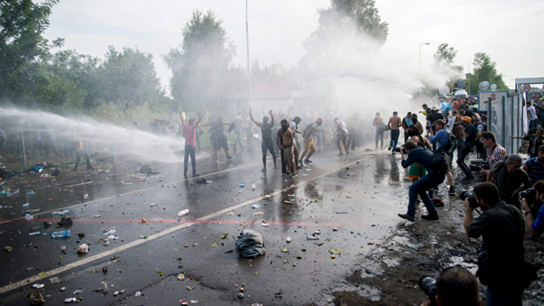 Sept. 16, 2015: Hungarian police use water canons against migrants at the Hungary-Serbia border crossing.