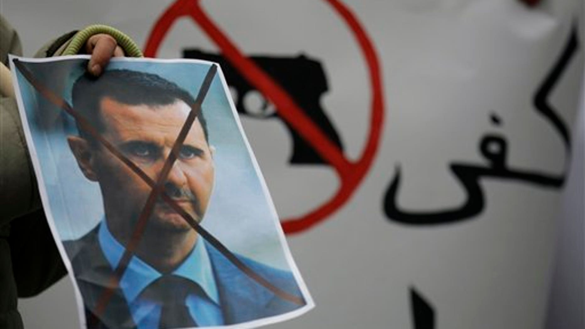 Dec. 23: A Syrian immigrant holds a crossed out depiction of Syrian President Bashar al-Assad during a rally against his regime in front of the Syrian embassy in Belgrade, Serbia.