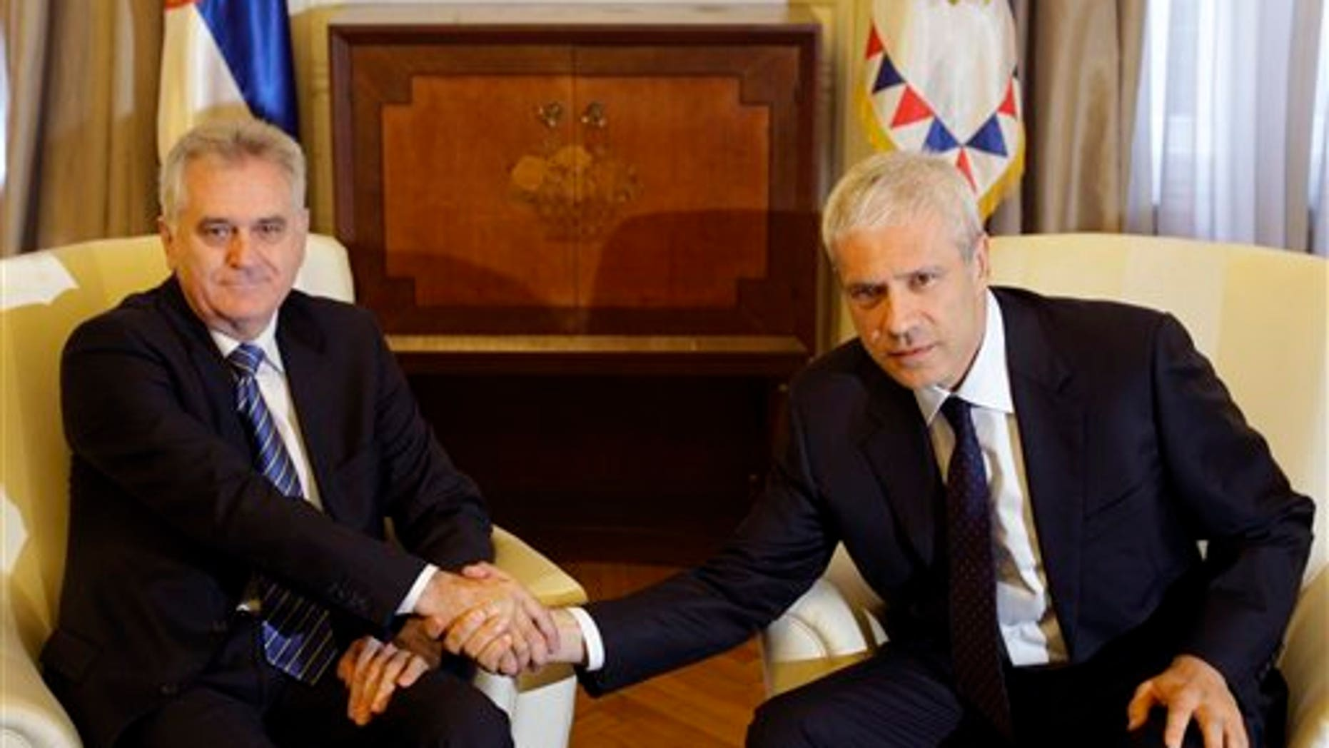 May 28, 2012: Newly elected Serbian President Tomislav Nikolic, left, shakes hands with former president Boris Tadic during meeting in the Serbian presidency building, in Belgrade, Serbia.