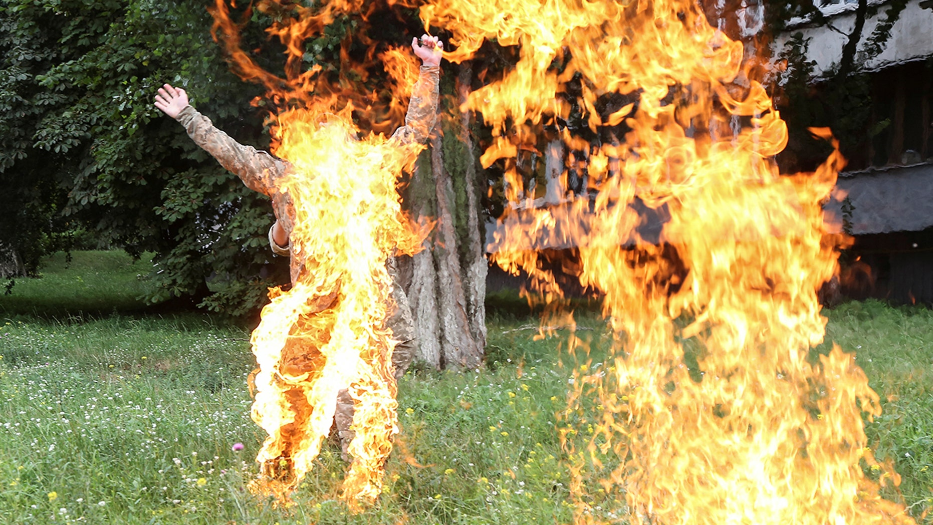 An officer on duty attempts to knock down the flame as former Ukrainian serviceman Serhii Ulianov sets himself on fire.