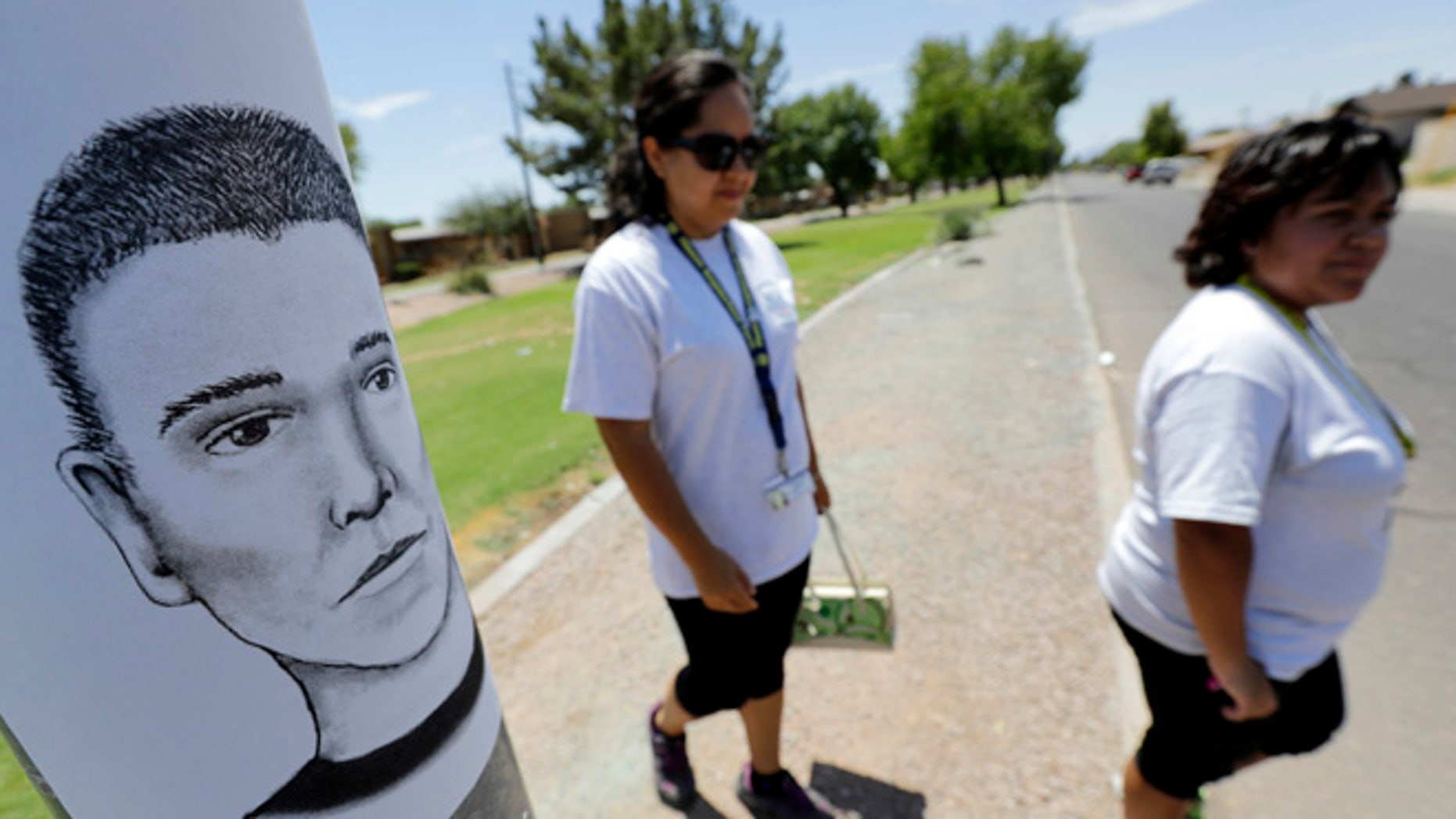 FILE--In this July 27, 2016, file photo, Phoenix neighborhood patrol officers Maribel Diaz Lopez, left, and Mario Ocampo walk Maryvale neighborhood streets in Phoenix, Ariz., to hand out an artist rendering of a suspected serial killer, as shown on the light pole, and block watch flyers. Authorities have released police reports on two of seven shooting deaths that investigators believed were carried out by a serial killer. The reports detail the shooting deaths of Manual Castro Garcia and Horacio de Jesus Pena, who died a week apart in June in the city's Maryvale neighborhood. (AP Photo/Matt York, file)