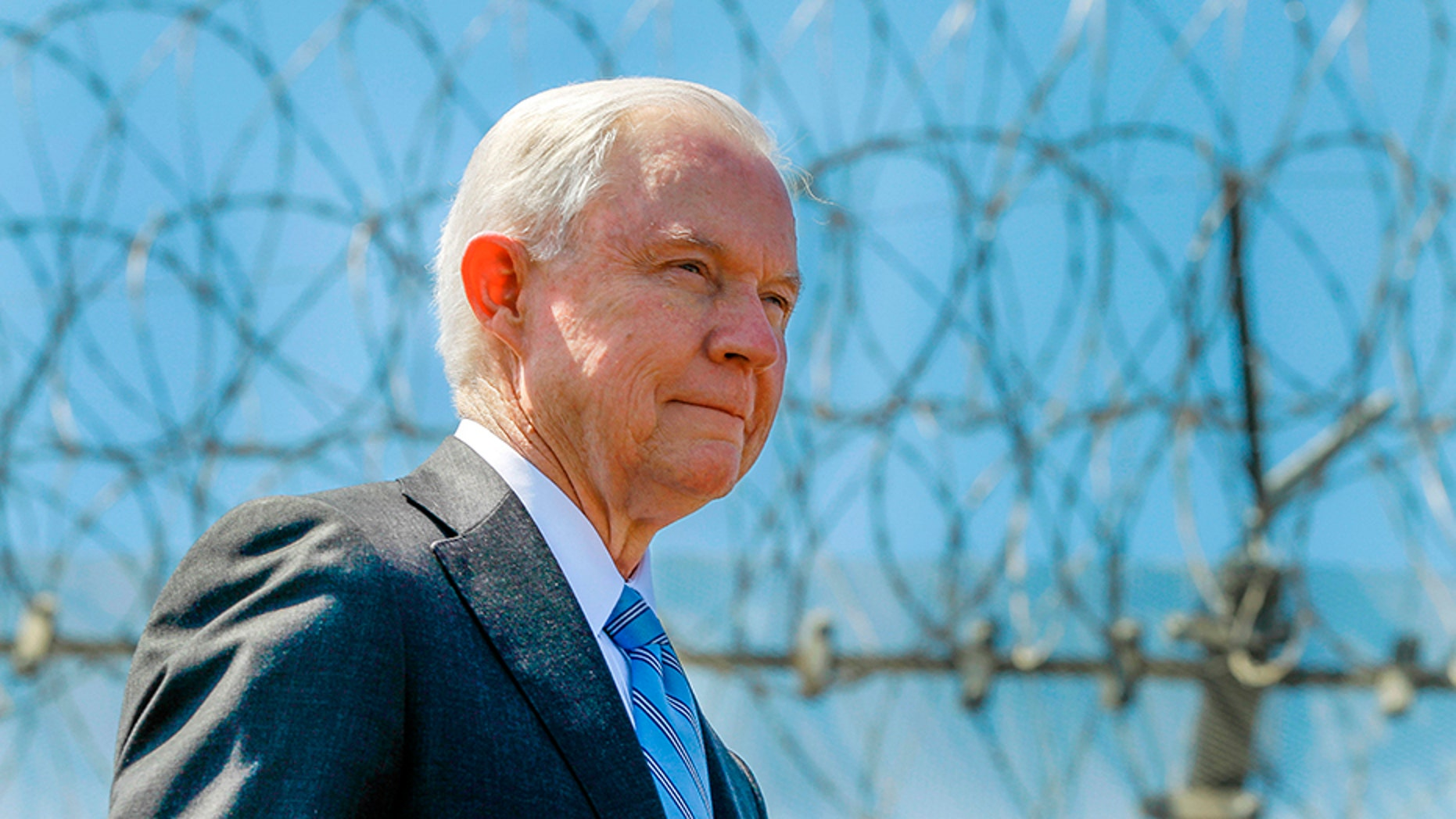 In April 21, 2017, file photo, Attorney General Jeff Sessions stands near a secondary border fence during a news conference at the U.S.-Mexican border next to the Brown Field Border Patrol Station in San Diego.