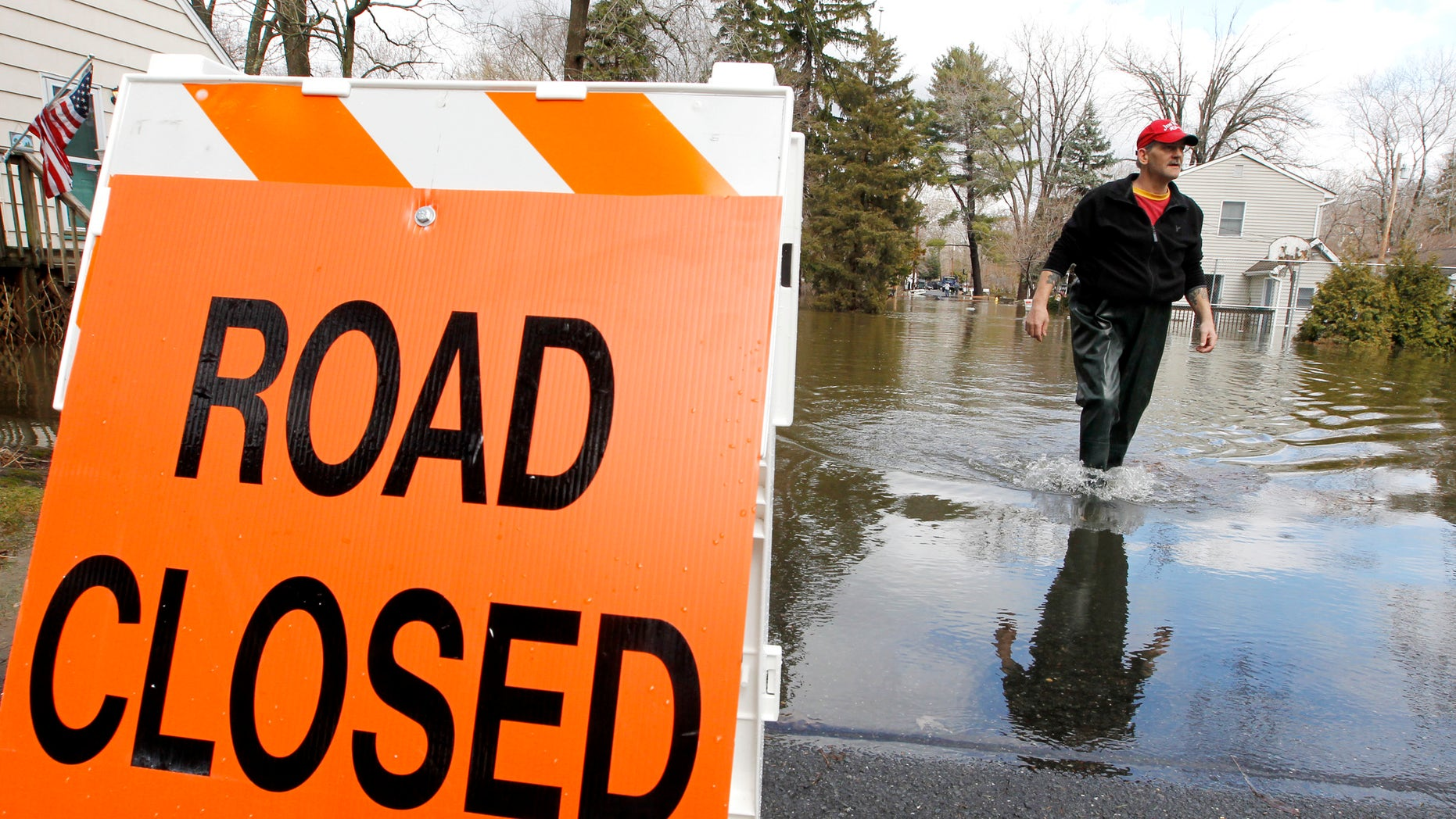 George Ruby, of the Riverview Community in Wayne, N.J., wades through water on his street, Friday, March 11, 2011. The water levels rose Friday morning, following a storm that hit the northern New Jersey region.