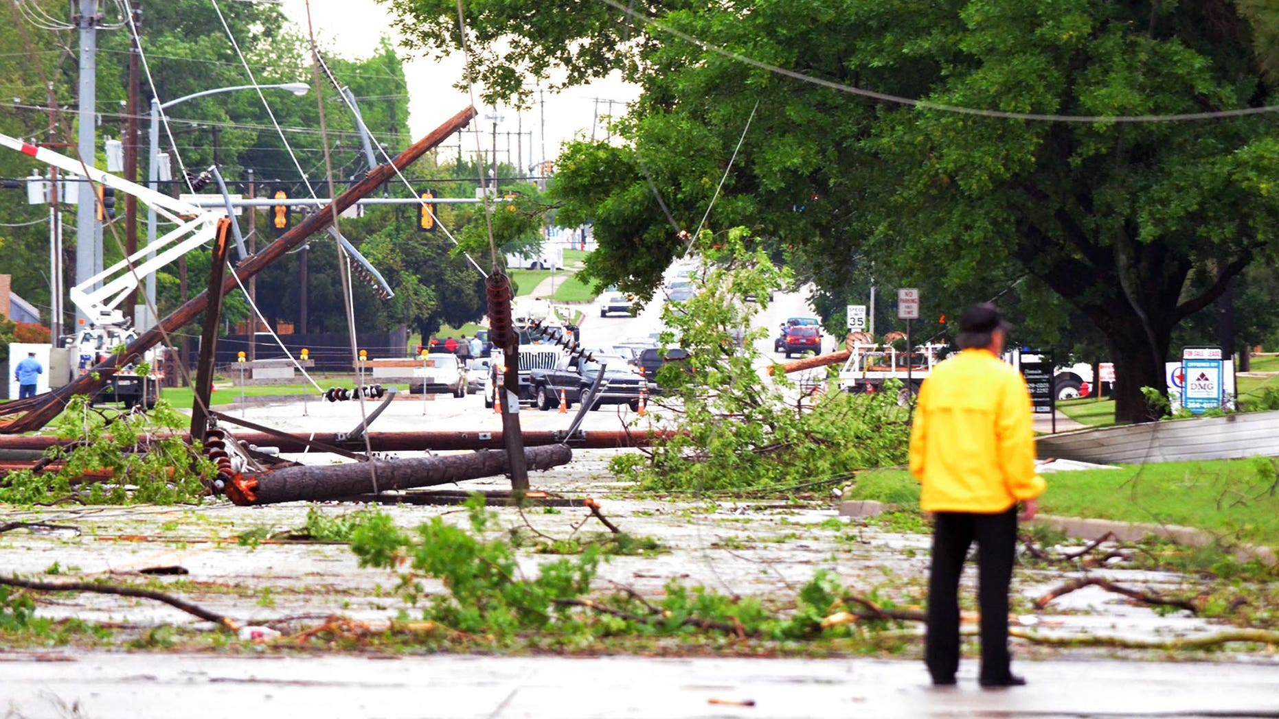 April 13, 2012: An emergency worker stands in the intersection of Lindsey Street and 24th Avenue Southwest after a tornado passed through, Friday afternoon in Norman, Okla