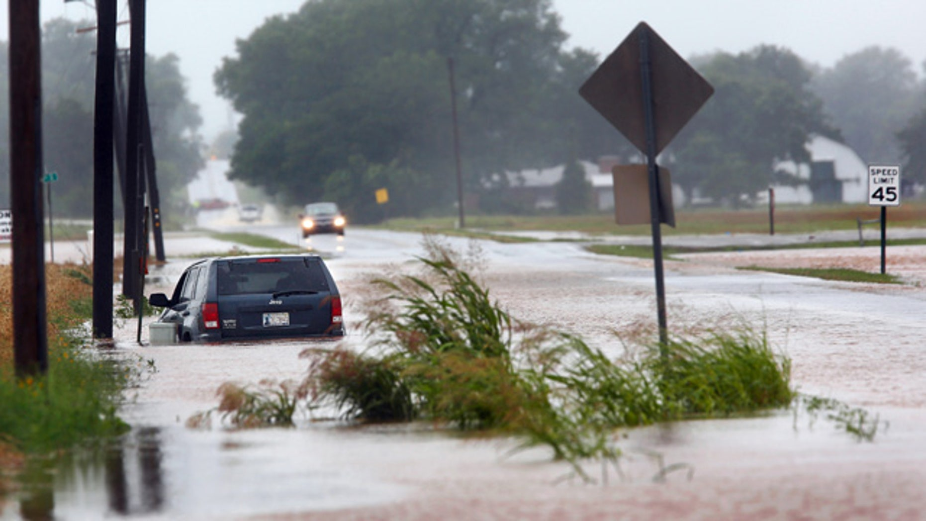 June 18, 2015: A vehicle is pointed the wrong direction after high water pushed it into a ditch on the south side of Hardesty Road west of US 177 in Shawnee, Okla. (Jim Beckel/The Oklahoman via AP)