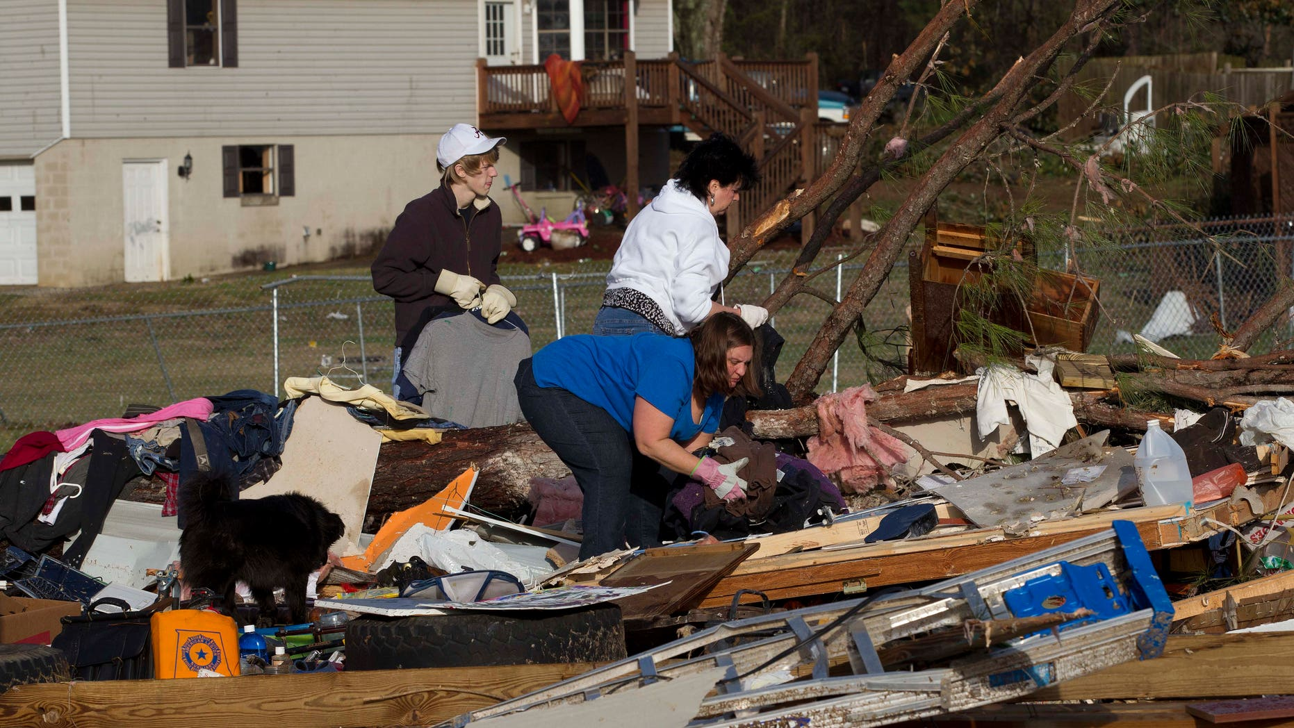 January 23: Neighbors and friends pick through the remains of Russ and Amber Butler's home in Oak Grove, Alabama, after a possible tornado passed through the area.