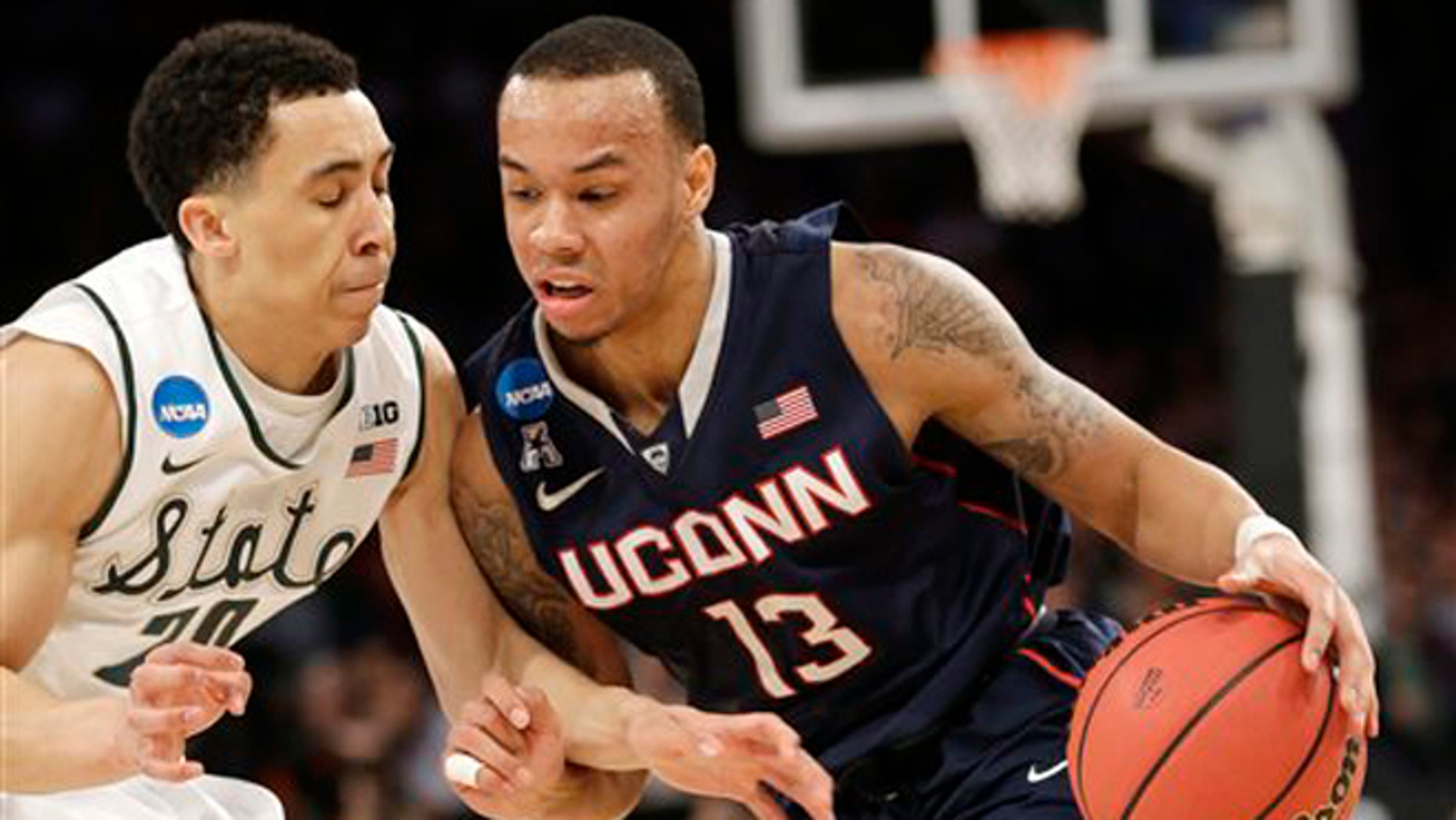 Connecticut's Shabazz Napier, right, moves the ball around Michigan State's Travis Trice in the first half of a regional final at the NCAA college basketball tournament on Sunday, March 30, 2014, in New York. (AP Photo/Seth Wenig)