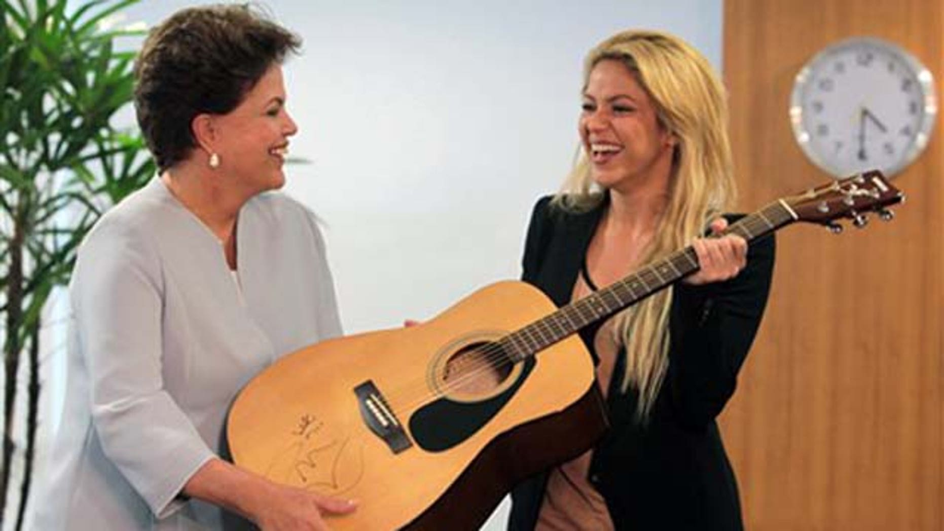 Brazil's President Dilma Rousseff, left, receives an autographed guitar from Colombian singer Shakira at Planalto Palace in Brasilia, Brazil, Thursday March 17, 2011. (AP Photo/Eraldo Peres)