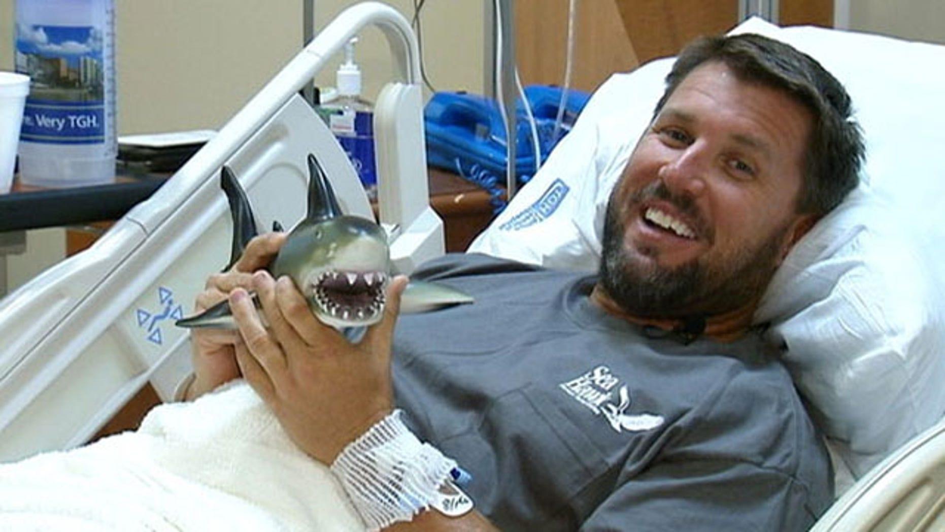 Shark bite survivor Erik Norrie plays with a toy shark a friend got him as a joke.