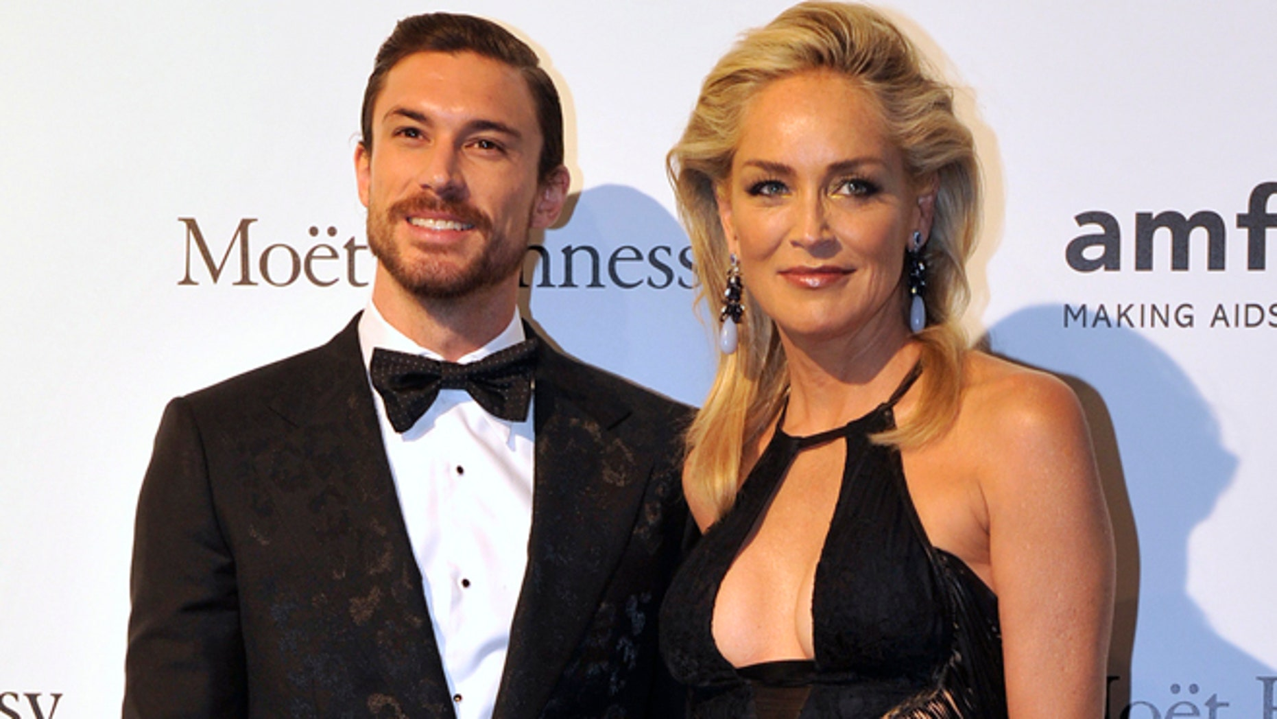 Actress Sharon Stone poses with her boyfriend Martin Mica before the charity dinner for The Foundation for AIDS Research (amfAR)'s during Milan's Fashion Week September 22, 2012.