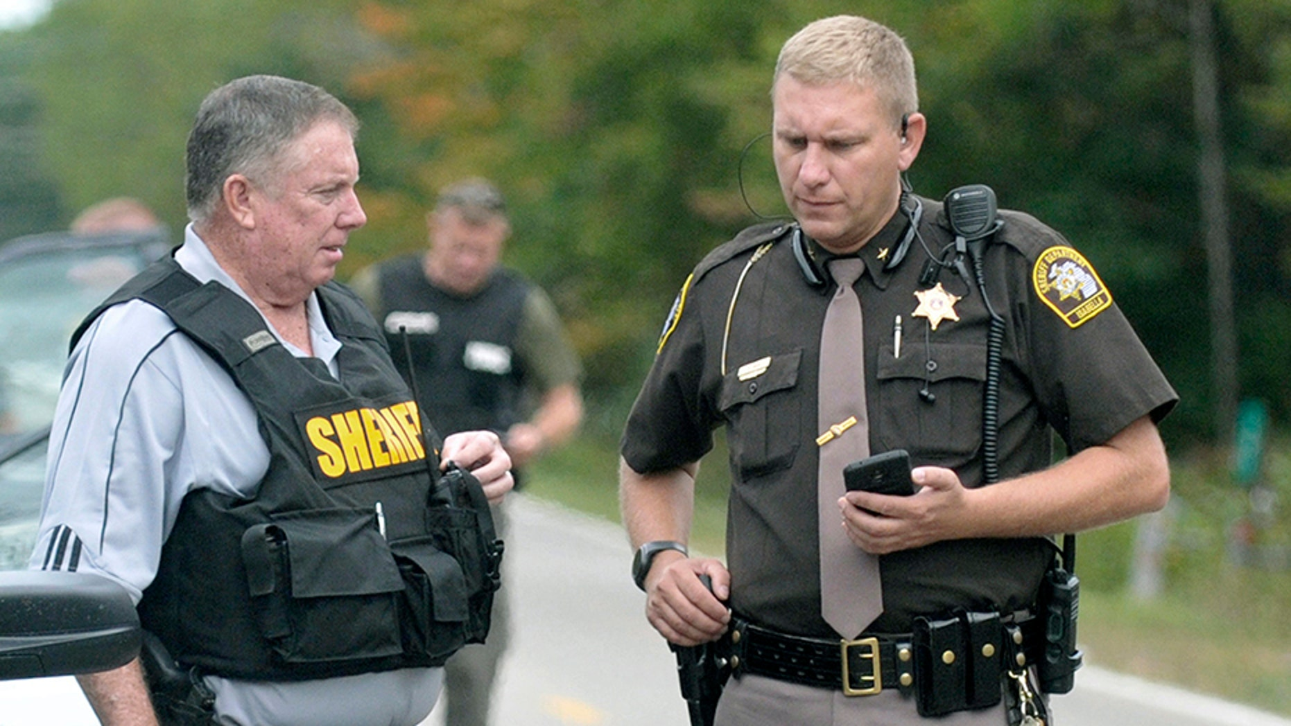 In this Sept. 27, 2017, photo, Isabella County Sheriff Michael Main, right, coordinates efforts in a police manhunt to locate a suspect in Michigan. Main is back in the news now, apologizing for accidentally leaving his gun in a mid-Michigan school gym locker room.