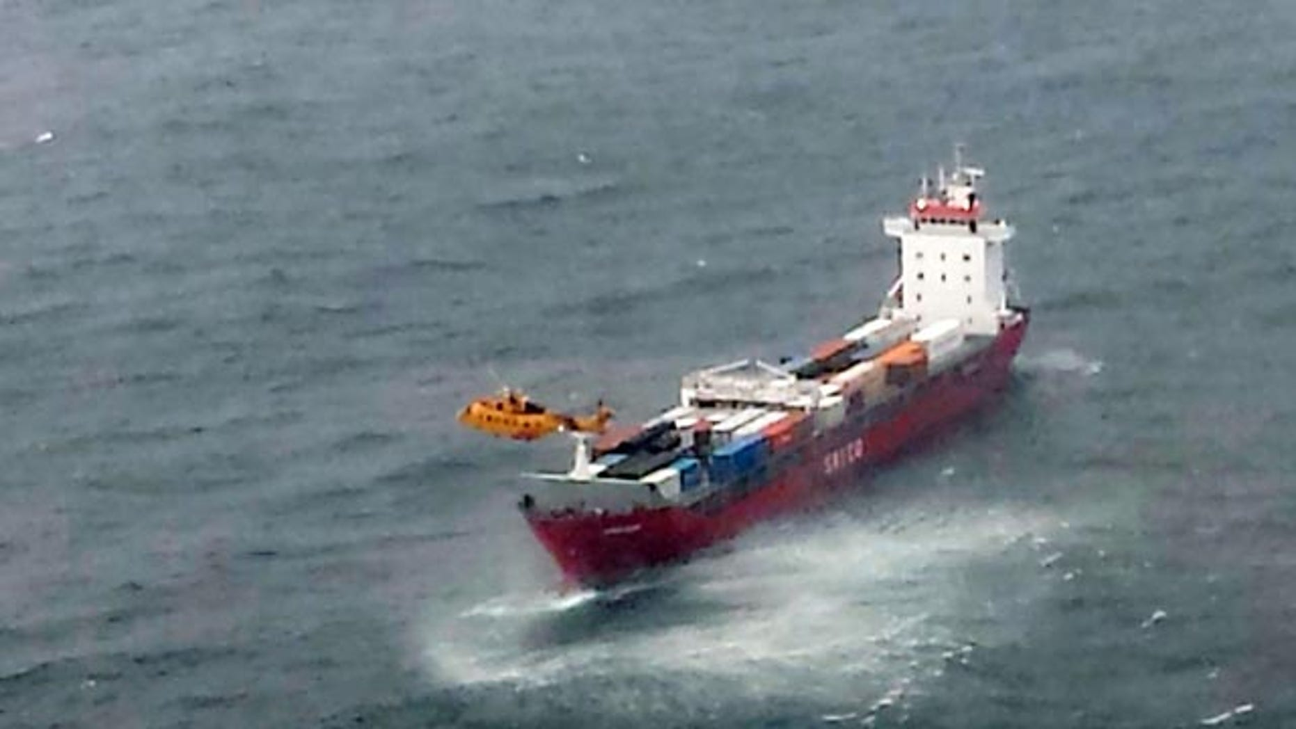 October 17, 2014: In this aerial photo provided by the Department of National Defense Maritime Forces Pacific, a Canadian Coast Guard helicopter flies near a Russian container ship carrying hundreds of tons of fuel drifting without power in rough seas off British Columbia's northern coast. (AP Photo/The Canadian Press, Department of National Defense Maritime Forces Pacific)