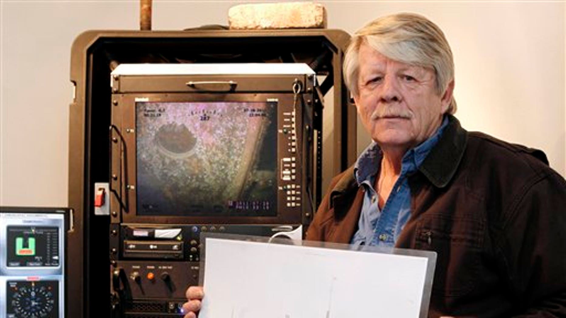 Feb. 1: Greg Brooks, co-manager of Sub Sea Research, is seen aboard the salvage ship Sea Hunter in Boston Harbor holding a picture of the British merchant ship Port Nicholson, which was sunk by a German U-boat in 1942 with a cargo of 71 tons of platinum now worth about $3 billion.