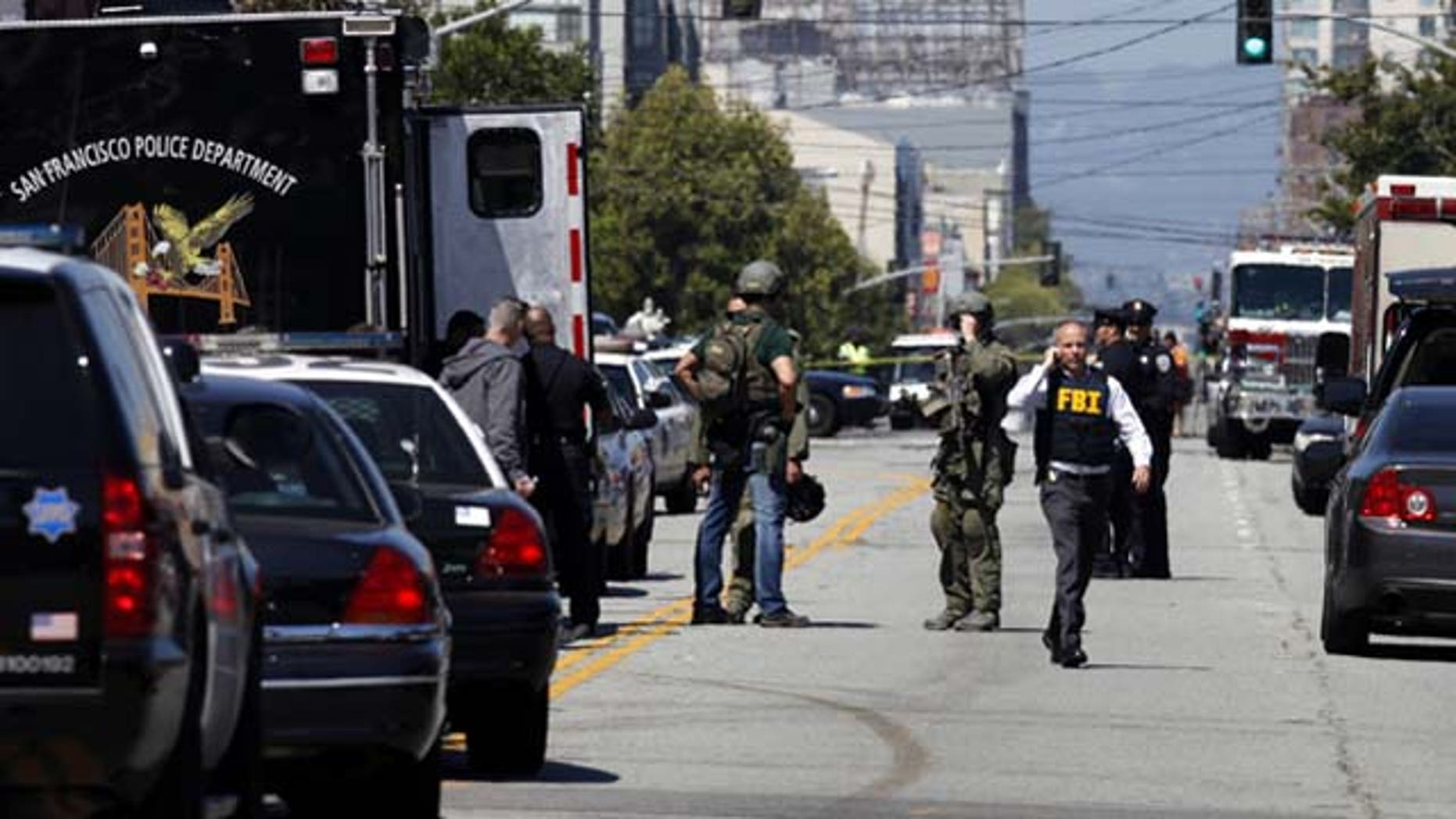 July 12, 2013: San Francisco Police officers and FBI officials work the scene near at Eighth Street and Brannan Street after a shooting. Two women were killed and a man was wounded on Friday before a suspect covered in blood was arrested at a shopping center in a crowded San Francisco neighborhood that is home to police headquarters and several tech companies  (AP Photo/San Francisco Chronicle, Katie Meek)