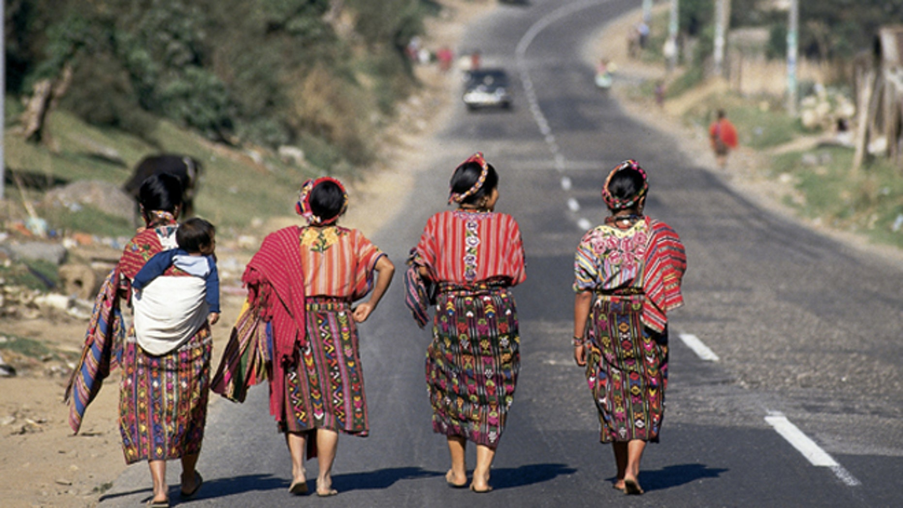 Four Guatemalan women walking down a paved highway near Cantel, Guatemala. (Photo by Independent Picture Service/UIG via Getty Images)