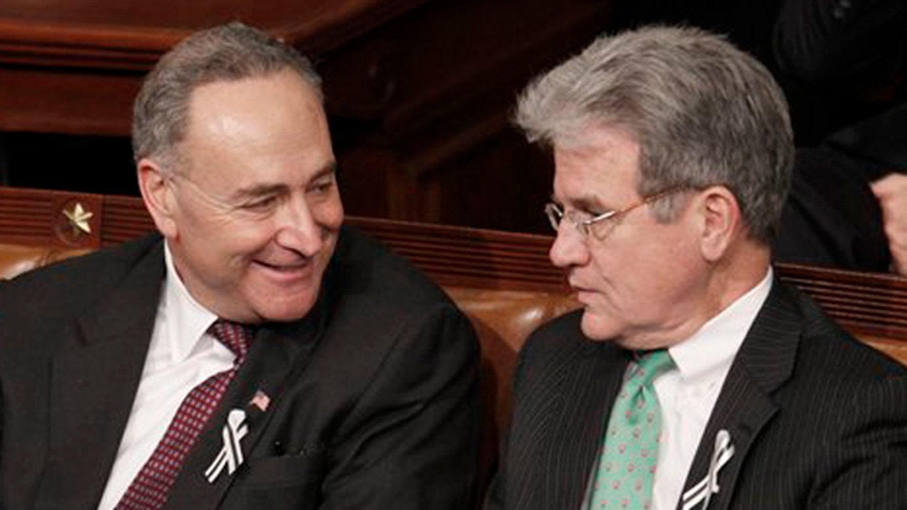 Sen, Charles Schumer, D-N.Y., left, talks with Sen. Tom Coburn, R-Okla., on Capitol Hill in Washington, during President Barack Obama's State of the Union address in Washington.