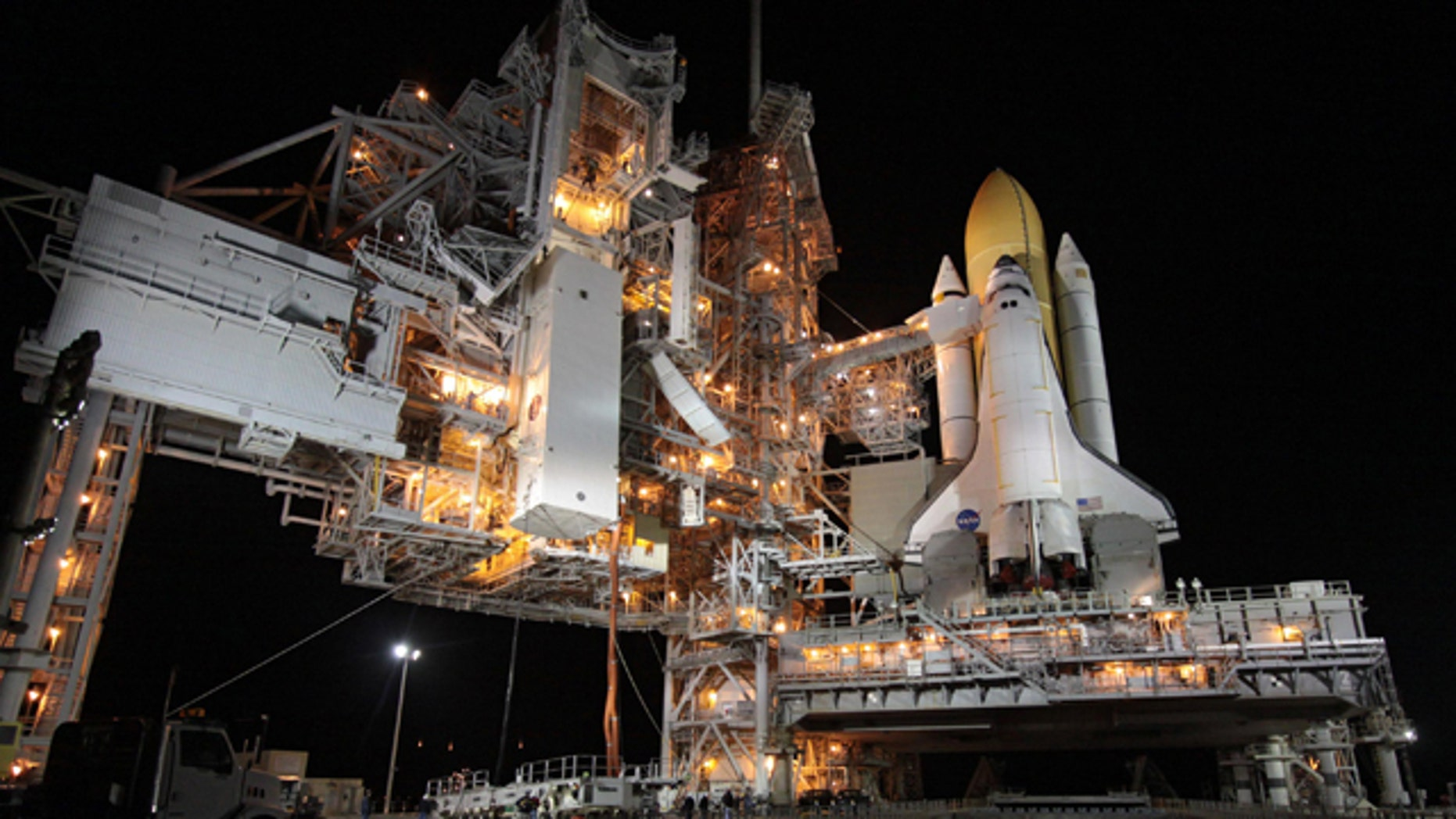 A transportation canister containing Tranquility, the International Space Station's Node 3, is lifted toward Space Shuttle Endeavour which rests at Launch Pad 39A.