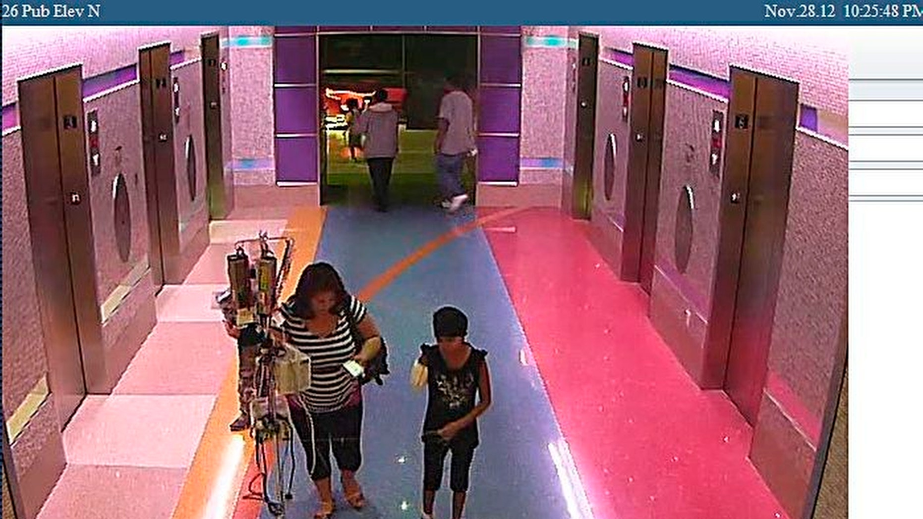 Dec. 3, 2012: In this hospital surveillance photo released by the Phoenix Police Department, a woman is seen with her 11-year-old daughter, a leukemia patient who had her arm amputated and a heart catheter inserted due to an infection.