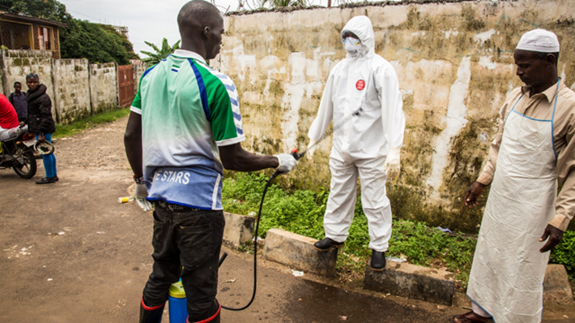 September 24, 2014: A health worker sprays disinfectant on a colleague after he assisted in the loading of a man suspected of suffering from the Ebola virus into an ambulance, in Freetown, Sierra Leone. (AP Photo/ Michael Duff)