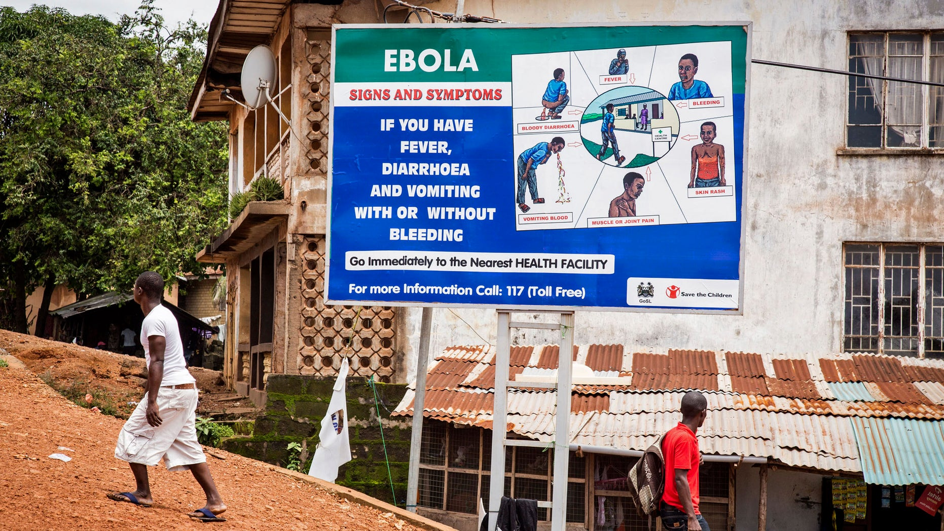 People walk past a billboard encouraging people suffering from symptoms linked to Ebola to present themselves at a health facility for treatment in Freetown, Sierra Leone, AP Photo