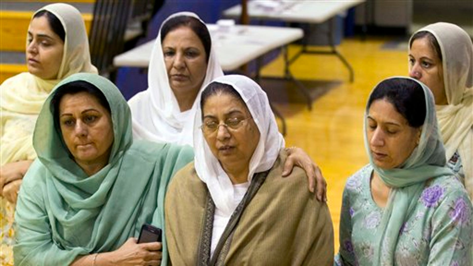 Aug. 10: Mourners grieve at the funeral and memorial service for the six victims of the Sikh Temple of Wisconsin mass shooting in Oak Creek, Wis. The public service was held in the Oak Creek High School. Three other people were wounded in the shooting last Sunday at the temple.