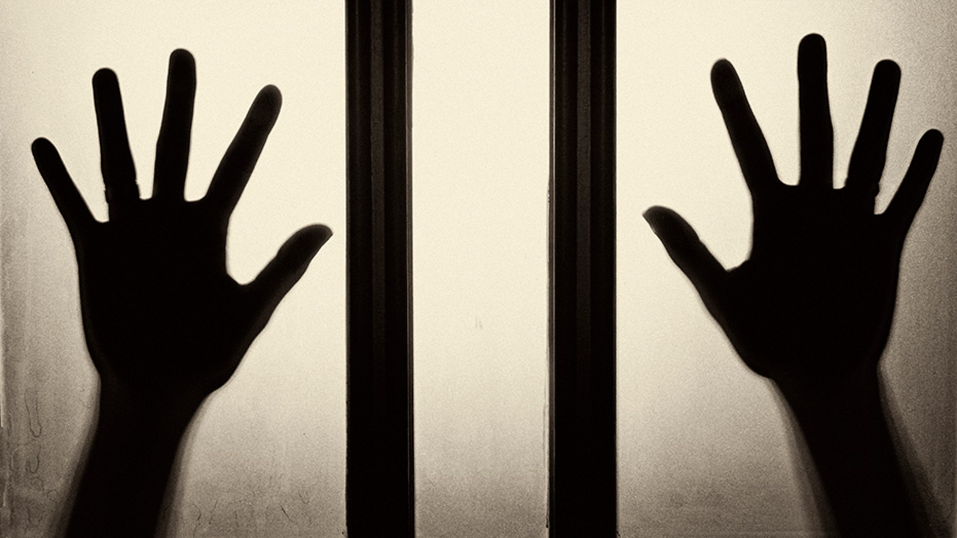Female hand silhouette on the glass