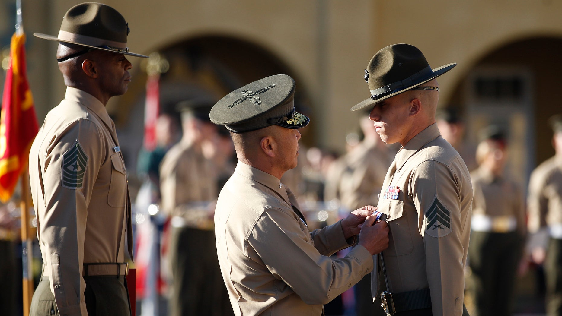 """Feb. 10, 2012: United States Marine Sgt. Philip A. McCulloch Jr., right, receives the Silver Star medal from Brigadier General Daniel D. Yoo for """"conspicuous gallantry and intrepidity in action"""" while serving in Afghanistan during a ceremony at the Marine Corp Recruit Depot."""