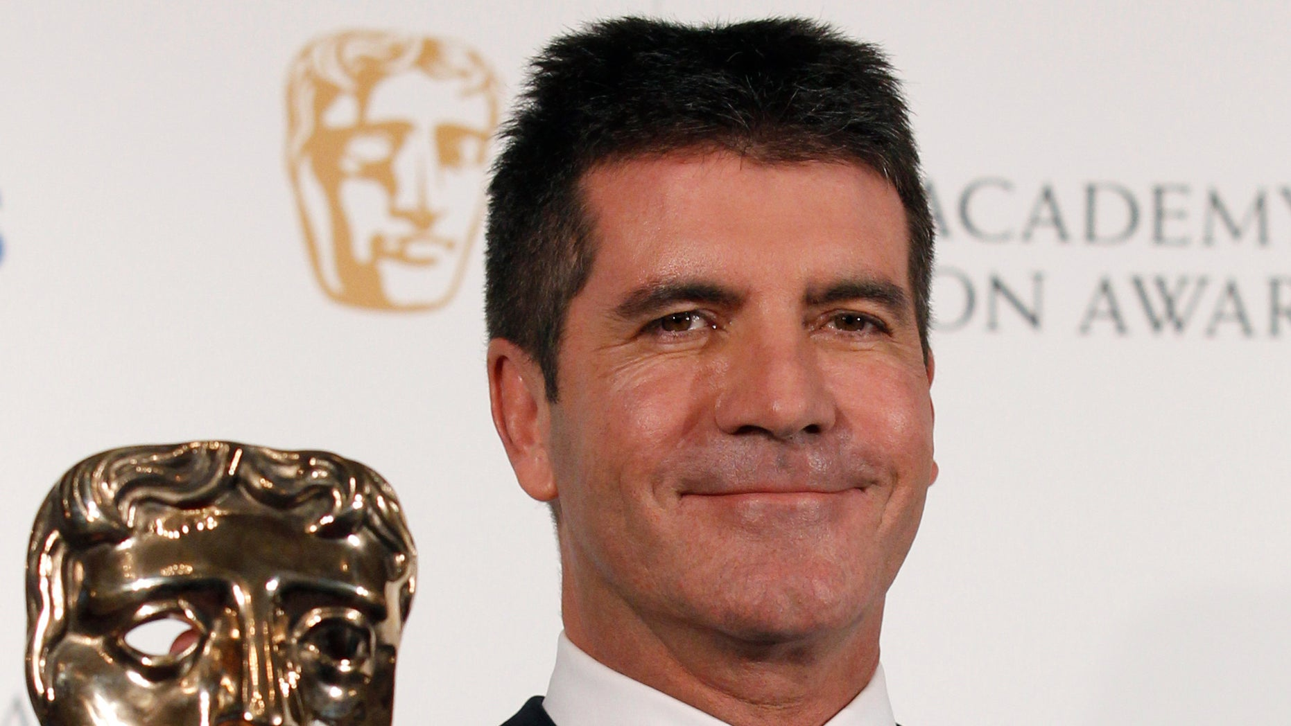 June 6: Television mogul Simon Cowell poses after receiving the British Academy Television Awards Special Award at the Palladium Theatre in London.
