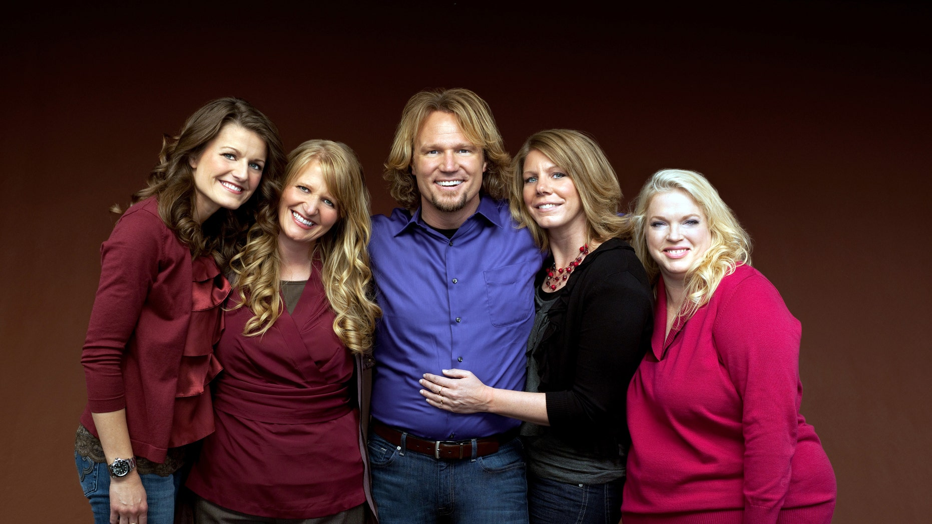 """Kody Brown, center, poses with his wives, from left, Robyn, Christine, Meri and Janelle, in a promotional photo for the reality series, """"Sister Wives"""" which aired in March, 2011."""