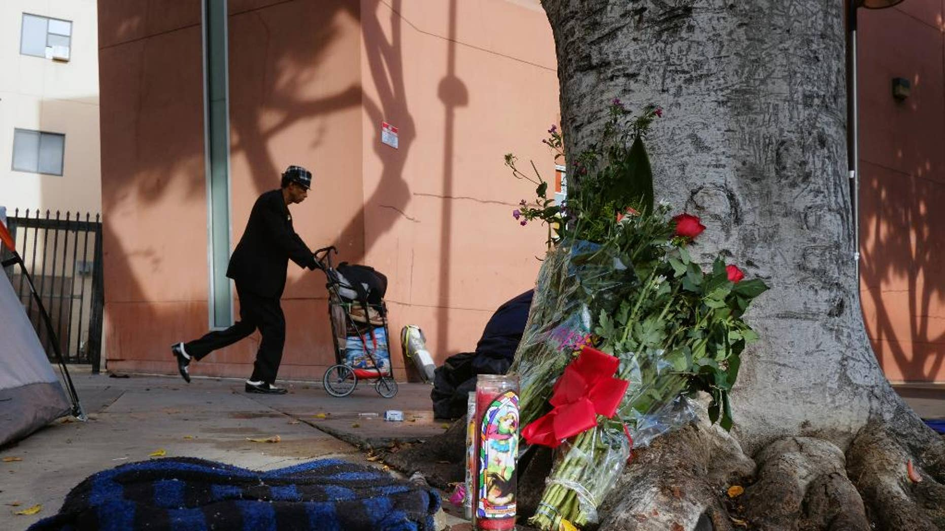FILE - This March 2, 2015 file photo shows a pedestrian walks past flowers and candles placed on a sidewalk near where Charly Keunang a homeless man was shot and killed by police in the Skid Row section of downtown Los Angeles. An officer dropped a nightstick during the struggle with Keunang and the woman who picked it up now faces an assault charge that could send her to prison for 25 years to life. The March shooting was captured on video, which shows Trishawn Cardessa Carey, 34, briefly lifting the baton as police scuffled with Keunang. (AP Photo/Richard Vogel,File)