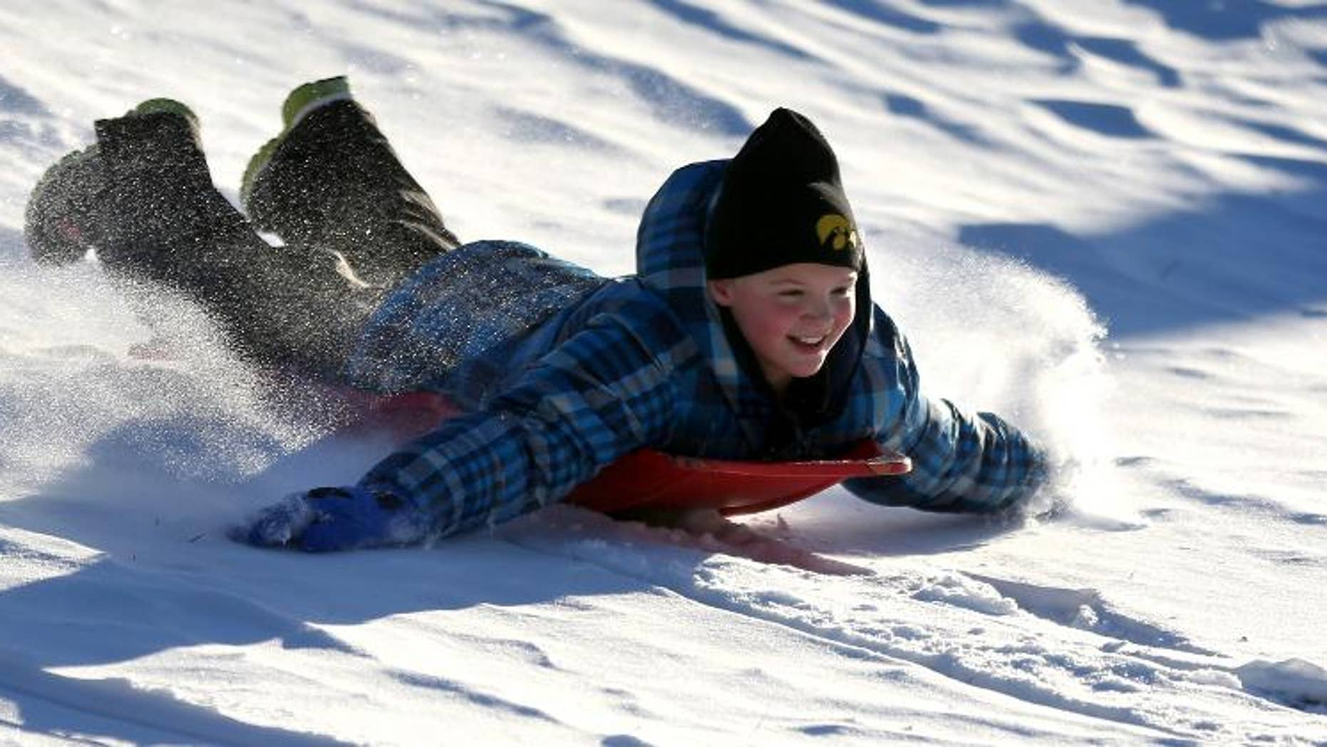 FILE - In this  Dec. 11, 2013 file photo Zoe Reisen,10, of Dubuque, Iowa, sleds down a hill at Allison-Henderson Park on in Dubuque, Iowa. Faced with the potential bills from people who are injured sledding, Dubuque is one of the cities across the country the is opting to close hills rather than face the risk of large liability claims. (AP Photo/The Telegraph Herald, Jessica Reilly, File)