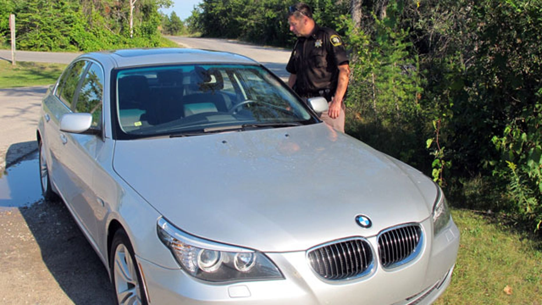 August 26, 2013: Mike Borkovich, sheriff of Leelanau County, Mich., examines a car parked at Sleeping Bear Dunes National Lakeshore that is believed to have been used by a missing man and his three children. The man, who is wanted on a domestic violence charge, and his children have been found safe. (AP Photo)