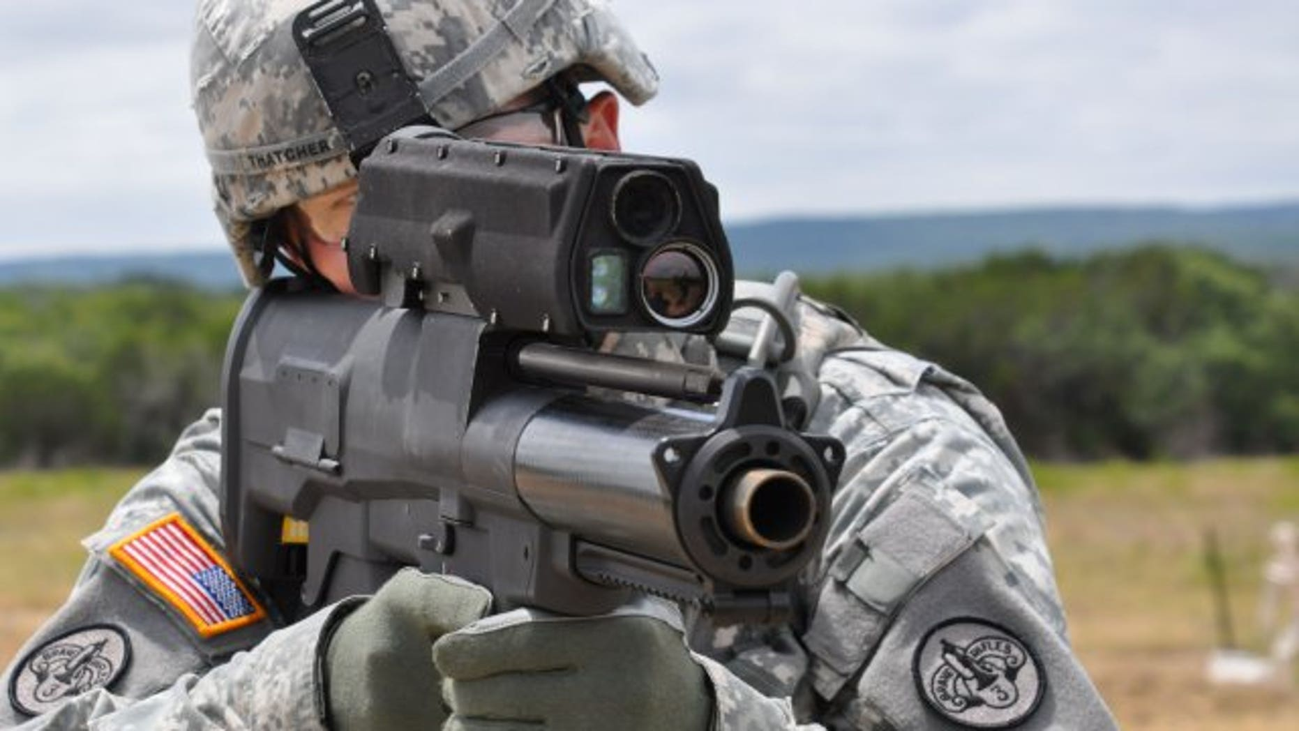 File photo - a soldier aims an XM25 Counter Defilade Target Engagement weapon system at Aberdeen Test Center, Md.