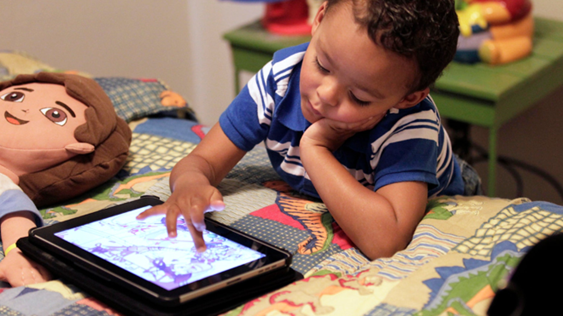 Frankie Thevenot, 3, plays with an iPad in his bedroom at his home in Metairie, La.  As of Wednesday, Aug. 7, 2013, the Campaign for a Commercial-Free Childhood, is urging federal investigators to examine the marketing practices of Fisher-Price's and Open Solution's mobile apps. It's the campaign's first complaint against the mobile app industry.