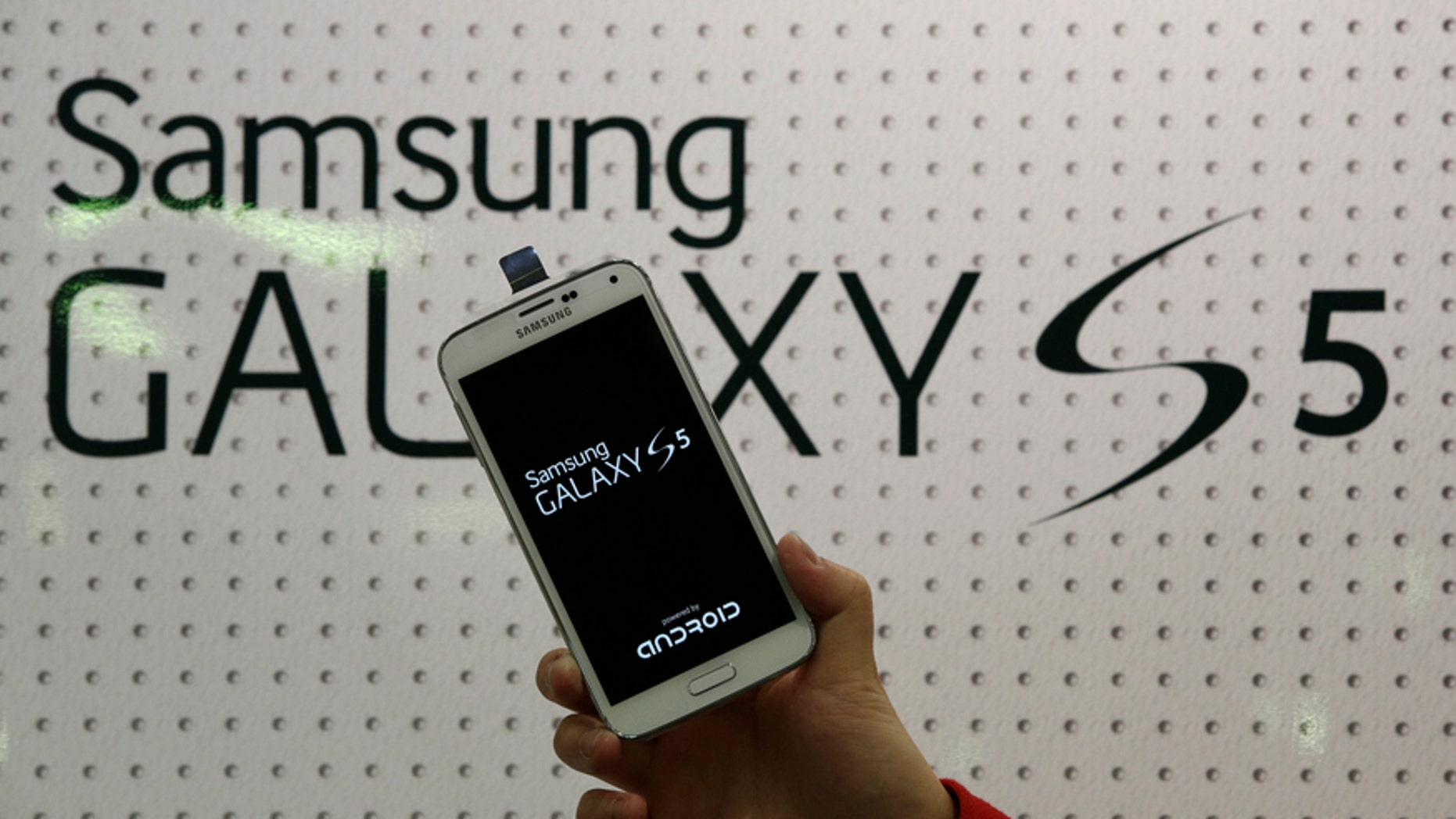An employee shows Samsung's Galaxy S5 smartphone at a mobile phone shop in Seoul, South Korea.