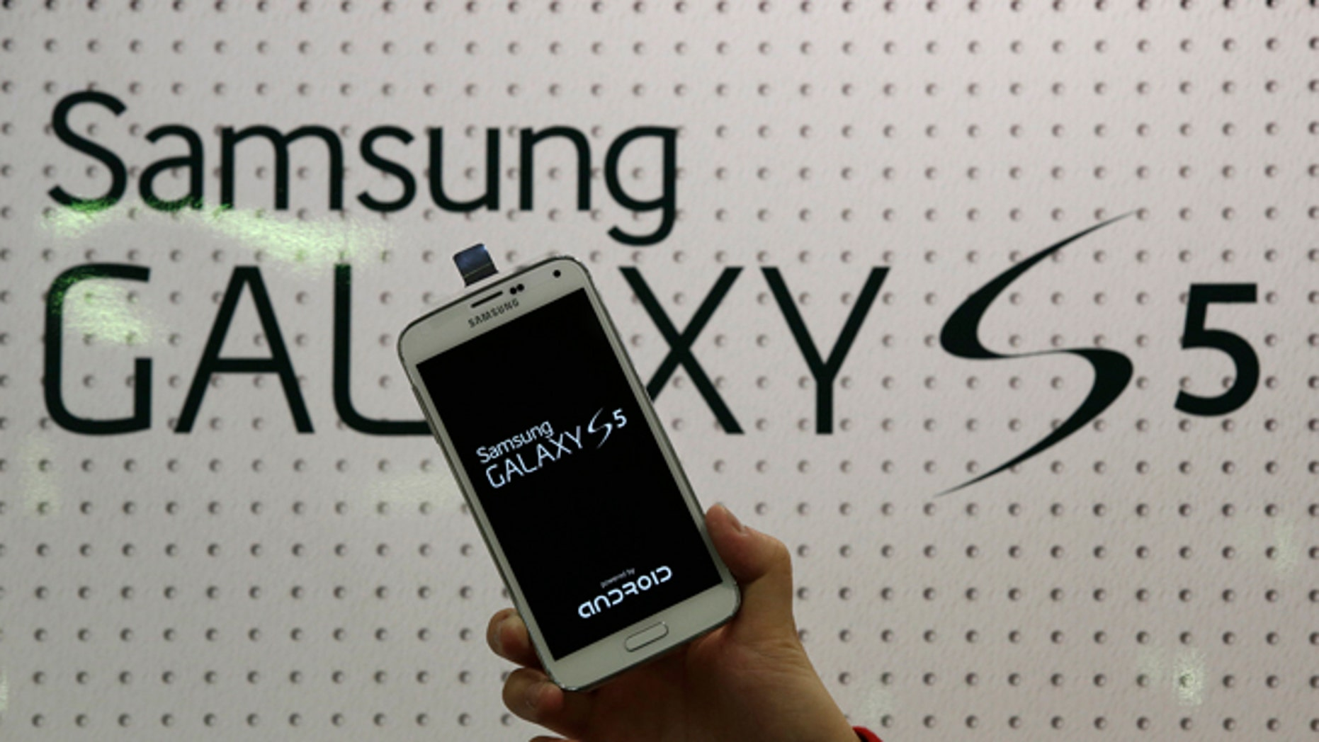 """FILE - An employee shows Samsung's Galaxy S5 smartphone at a mobile phone shop in Seoul, South Korea, in this March 27, 2014 file photo. Samsung Electronics will add two safeguards to its latest smartphone in an effort to deter rampant theft of the mobile devices nationwide, the company said Friday April 4, 2014. The world's largest mobile-phone maker said users will be able to activate for free its """"Find My Mobile"""" and """"Reactivation Lock"""" anti-theft features to protect the soon-to-be-released Galaxy 5 S.  (AP Photo/Lee Jin-man, File)"""