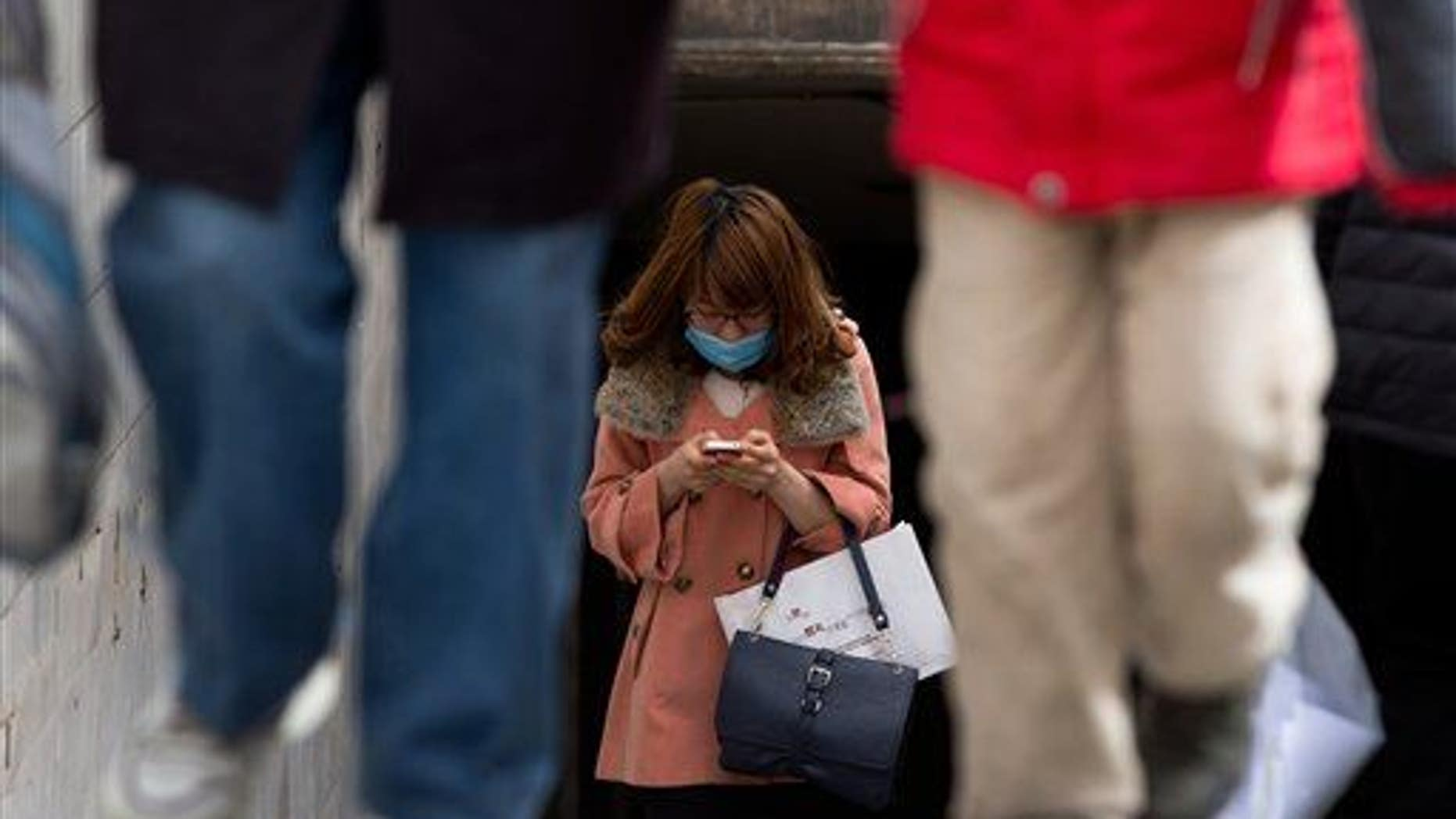 A Chinese woman wears a face mask checking her smartphone in Beijing.