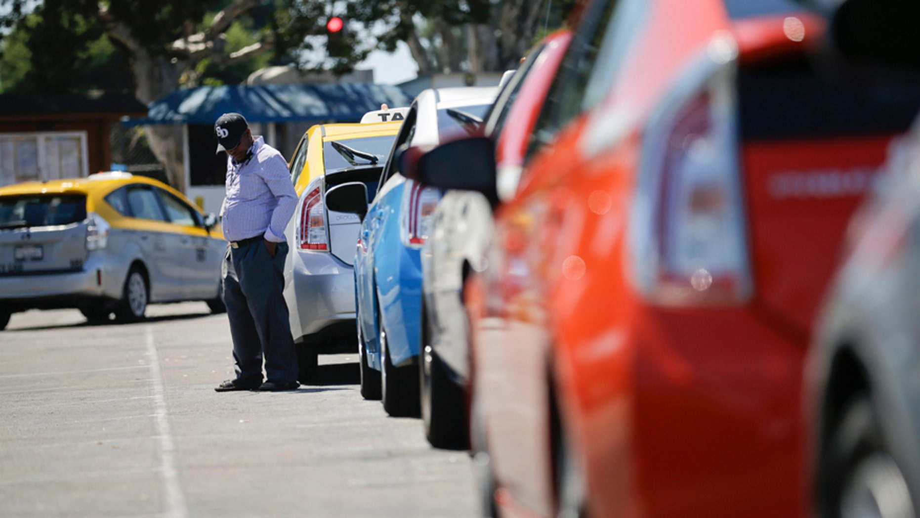 A cab driver waits near his car in line at a depot near the airport Wednesday, Sept. 10, 2014, in San Diego. Airport inspectors are judging how taxi drivers smell, a practice that some drivers say may lead to discrimination against immigrants. (AP Photo/Gregory Bull)